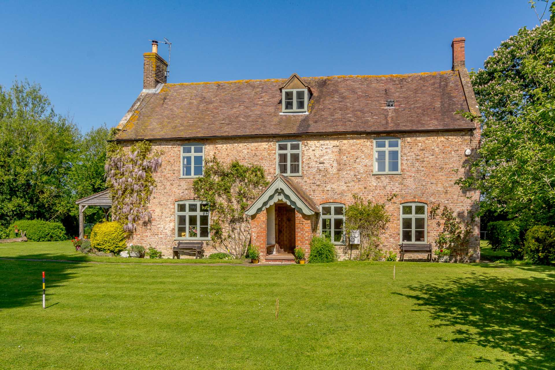 beautiful brick English country cottage home in countryside green windows