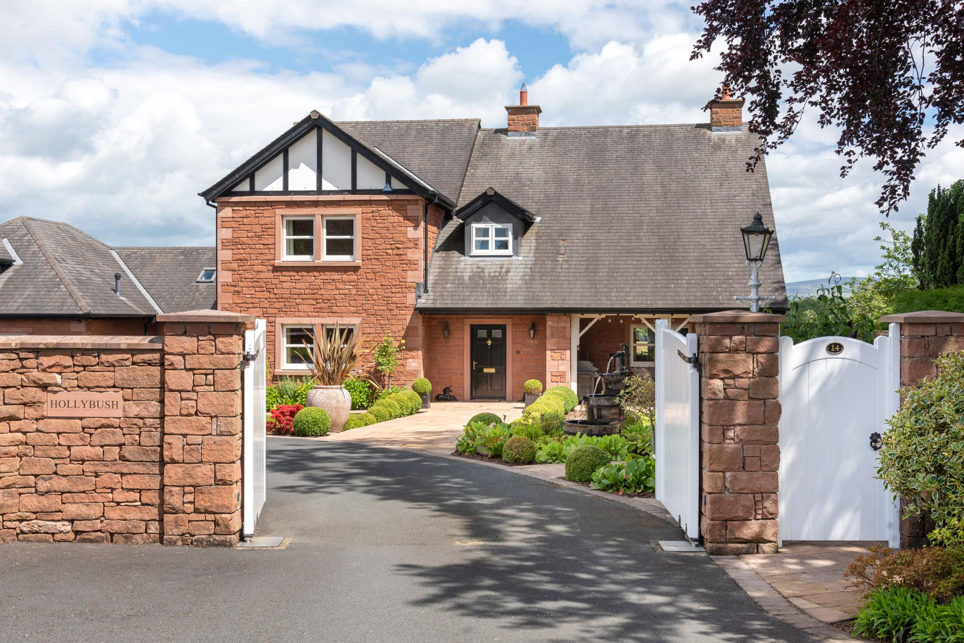 beautiful country home with landscaped gardens and white gates
