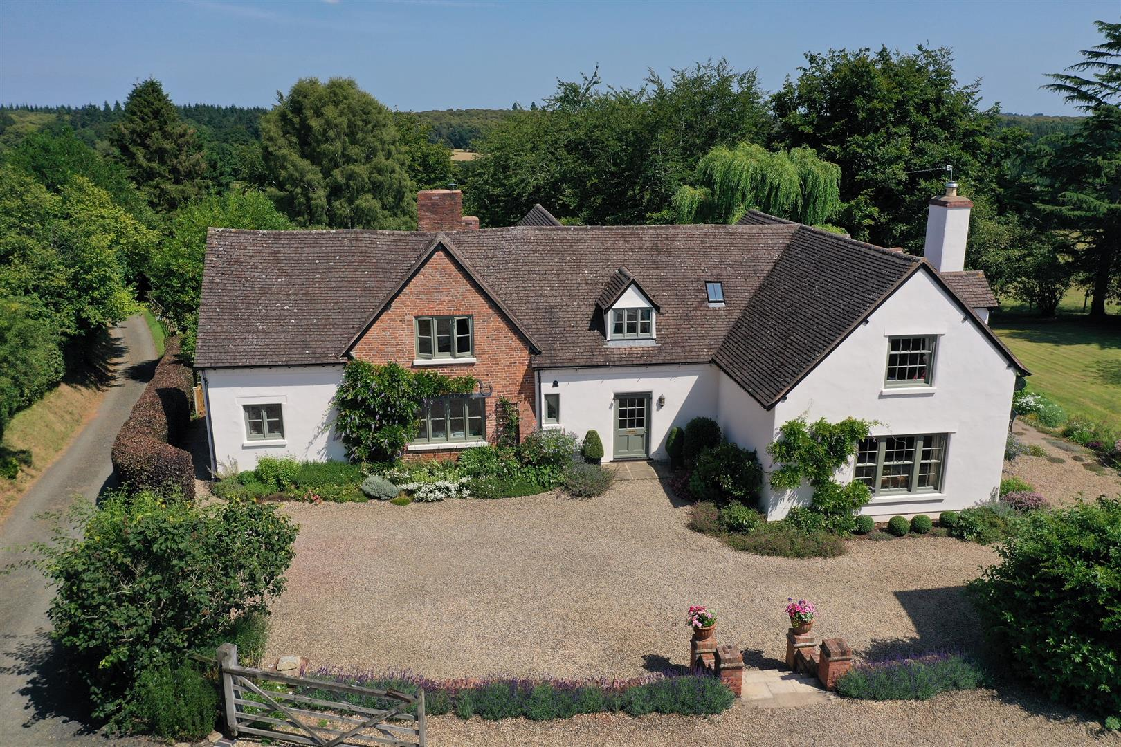 beautiful white brick English country cottage home with perfect gardens