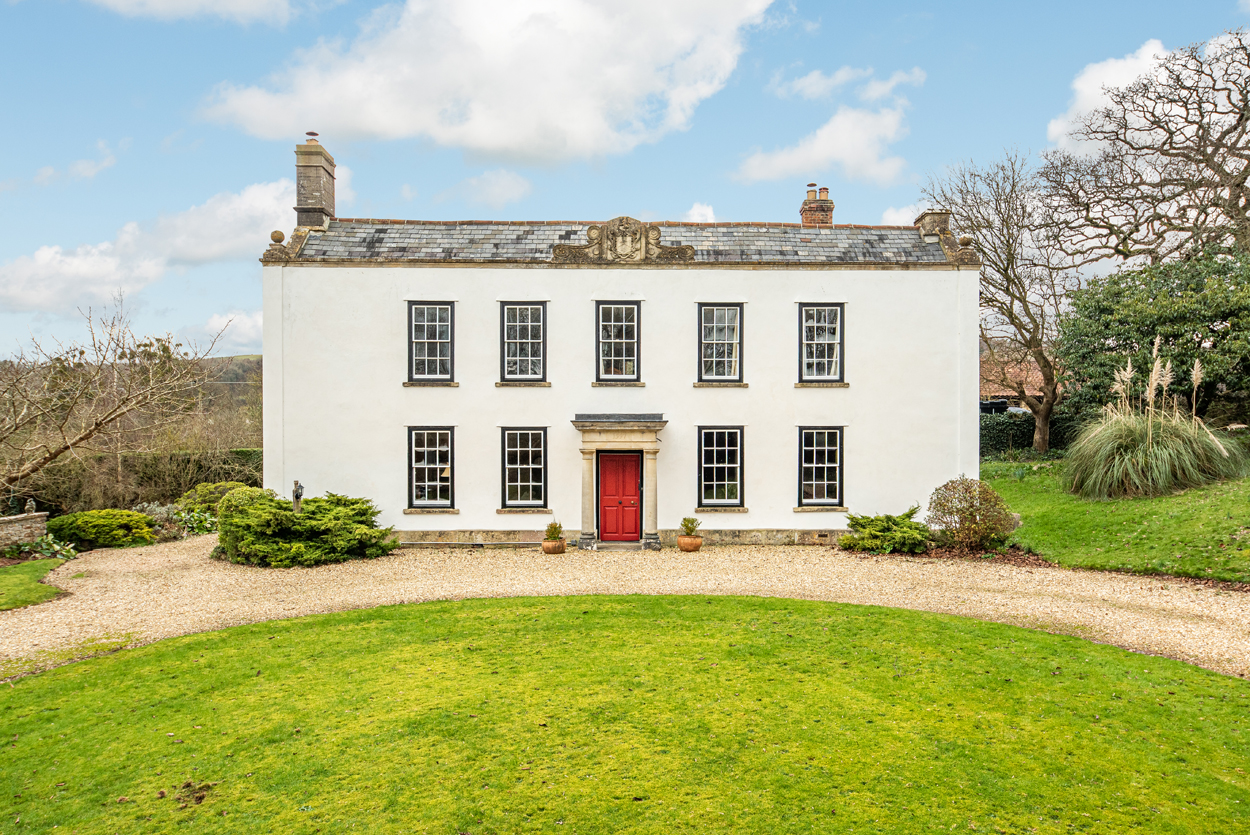 Georgian country manor house with white facade symmetrical and red door