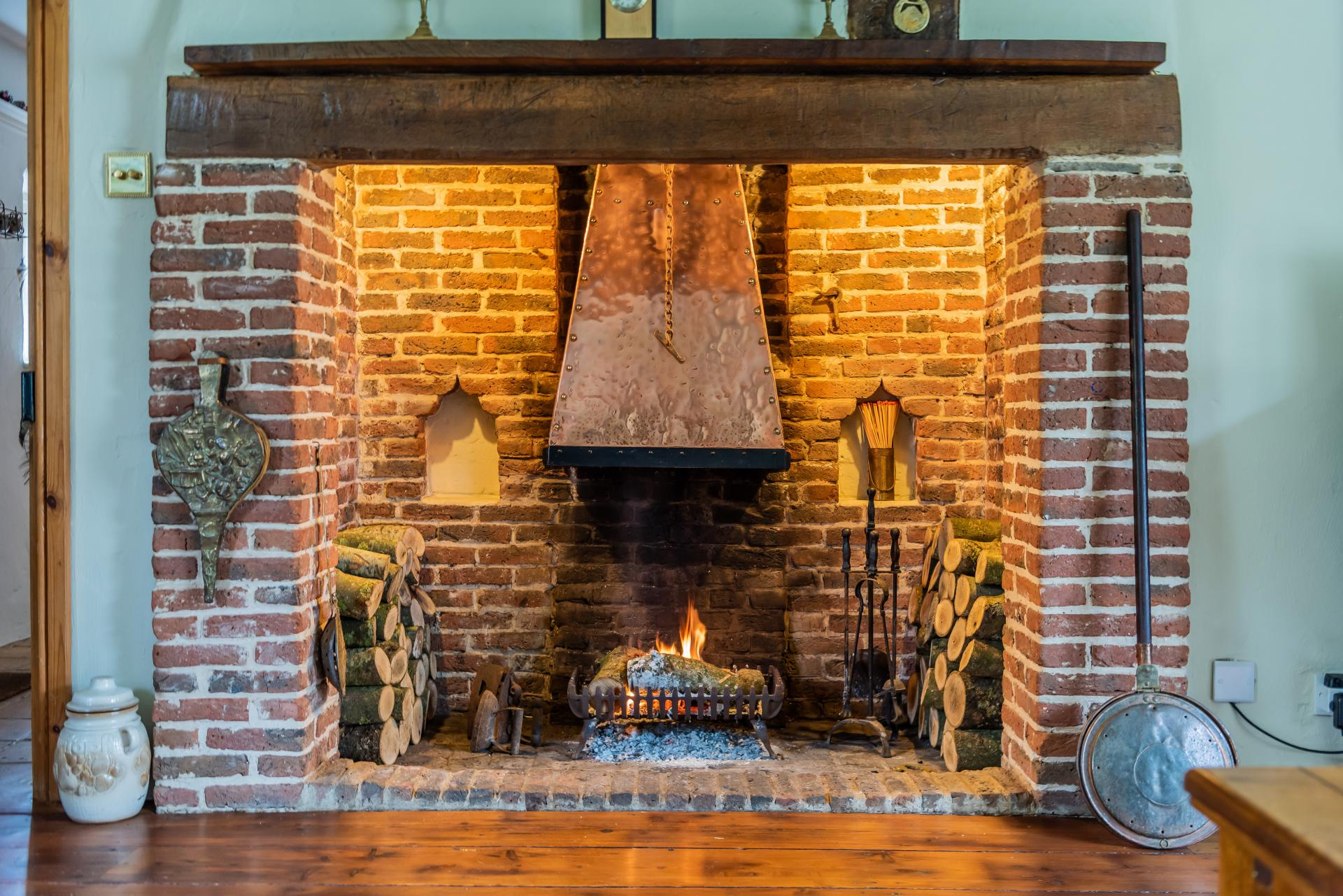 grand brick lined Inglenook fireplace with lit fire and logs