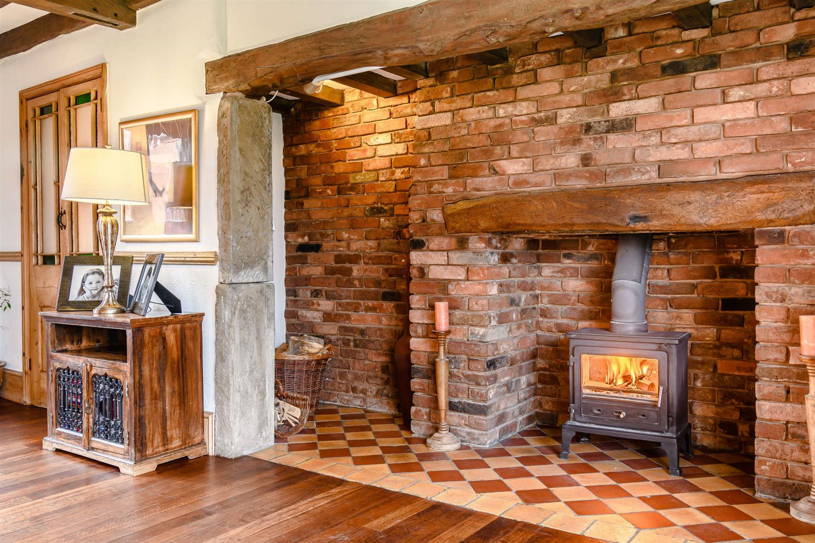grand English traditional brick fireplace with wood burning stove and tile base