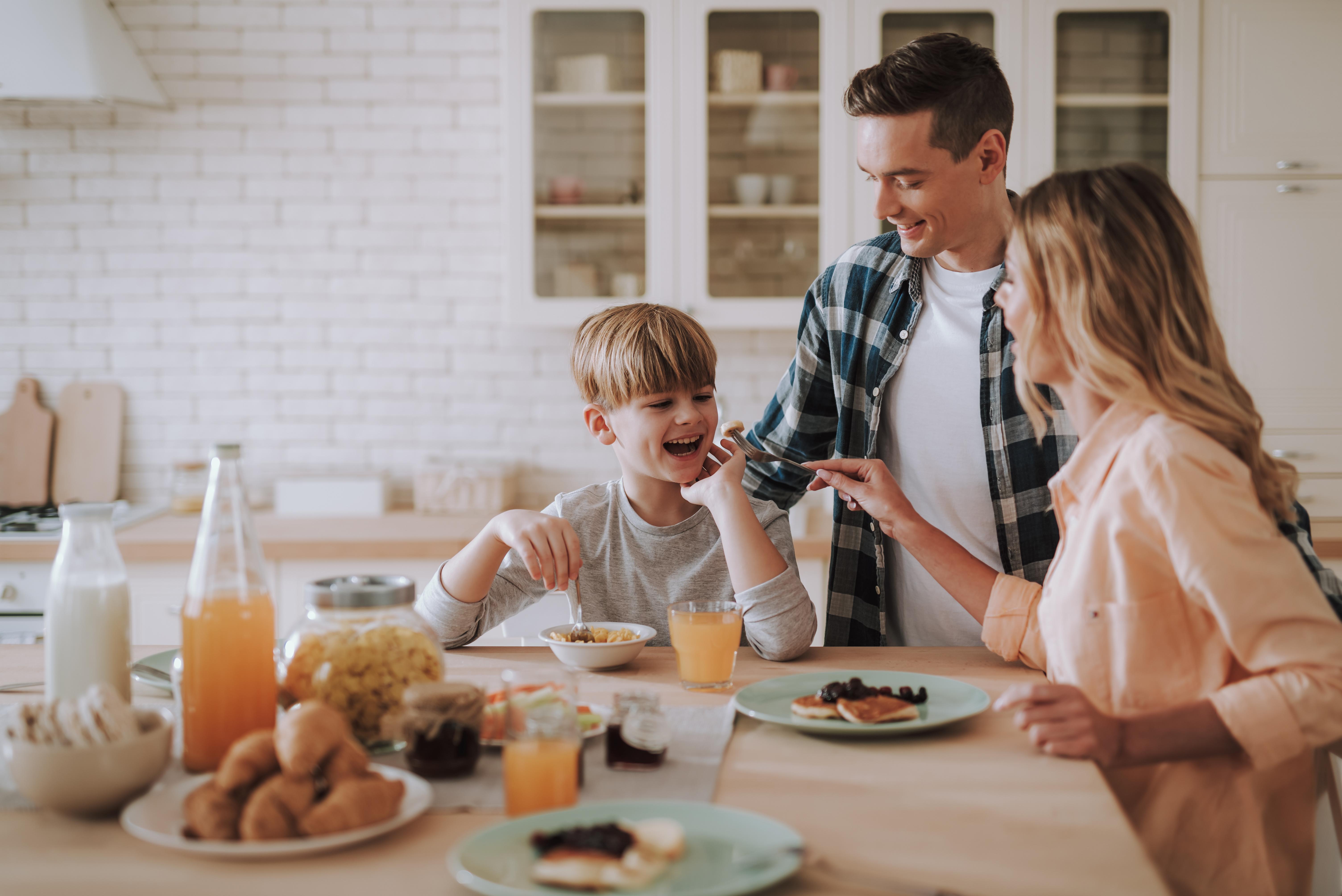 happy_kid_having breakfast with his parents