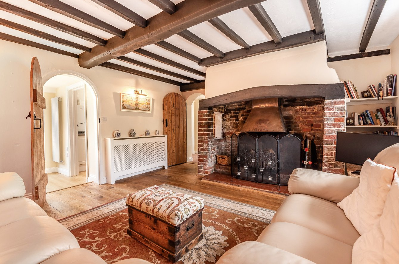living room with exposed beam and open Inglenook fireplace