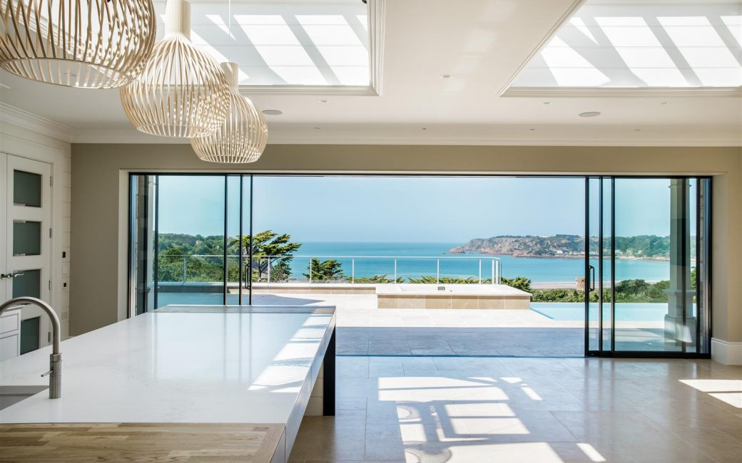 luxury contemporary interior design kitchen with sliding glass doors to sea