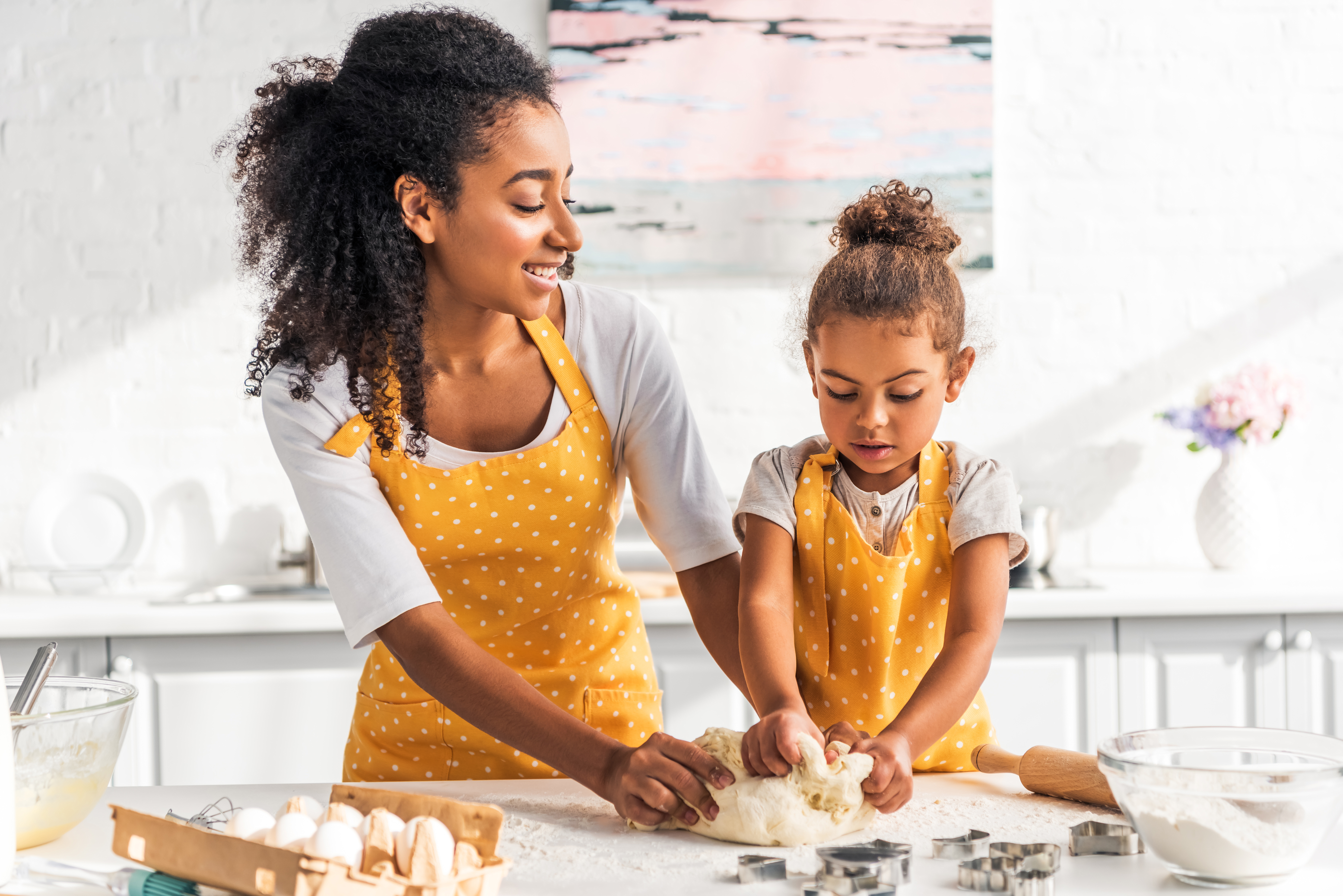 mother_and_daughter_kneading_dough_in_kitchen