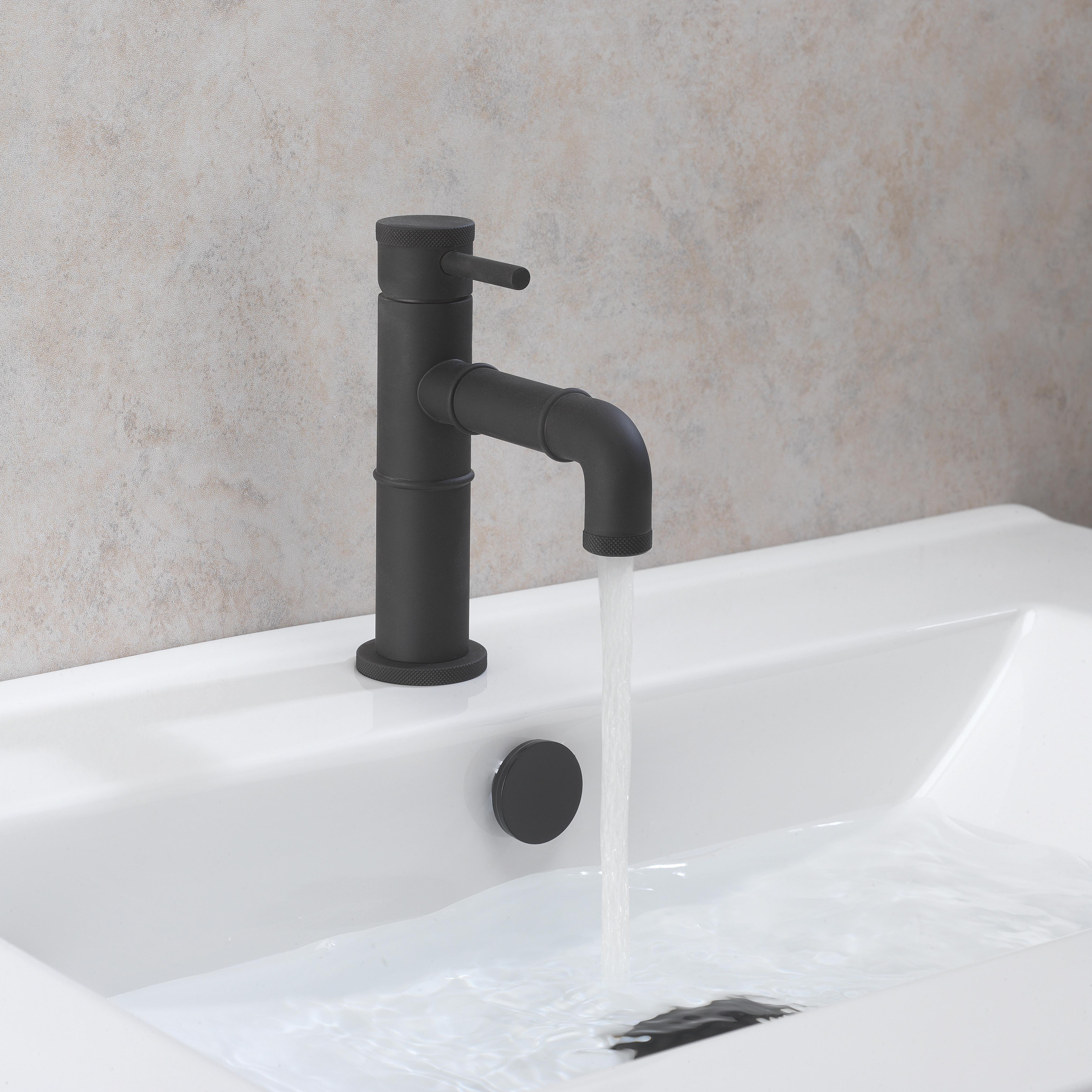 black tap fittings in plaster wall bathroom