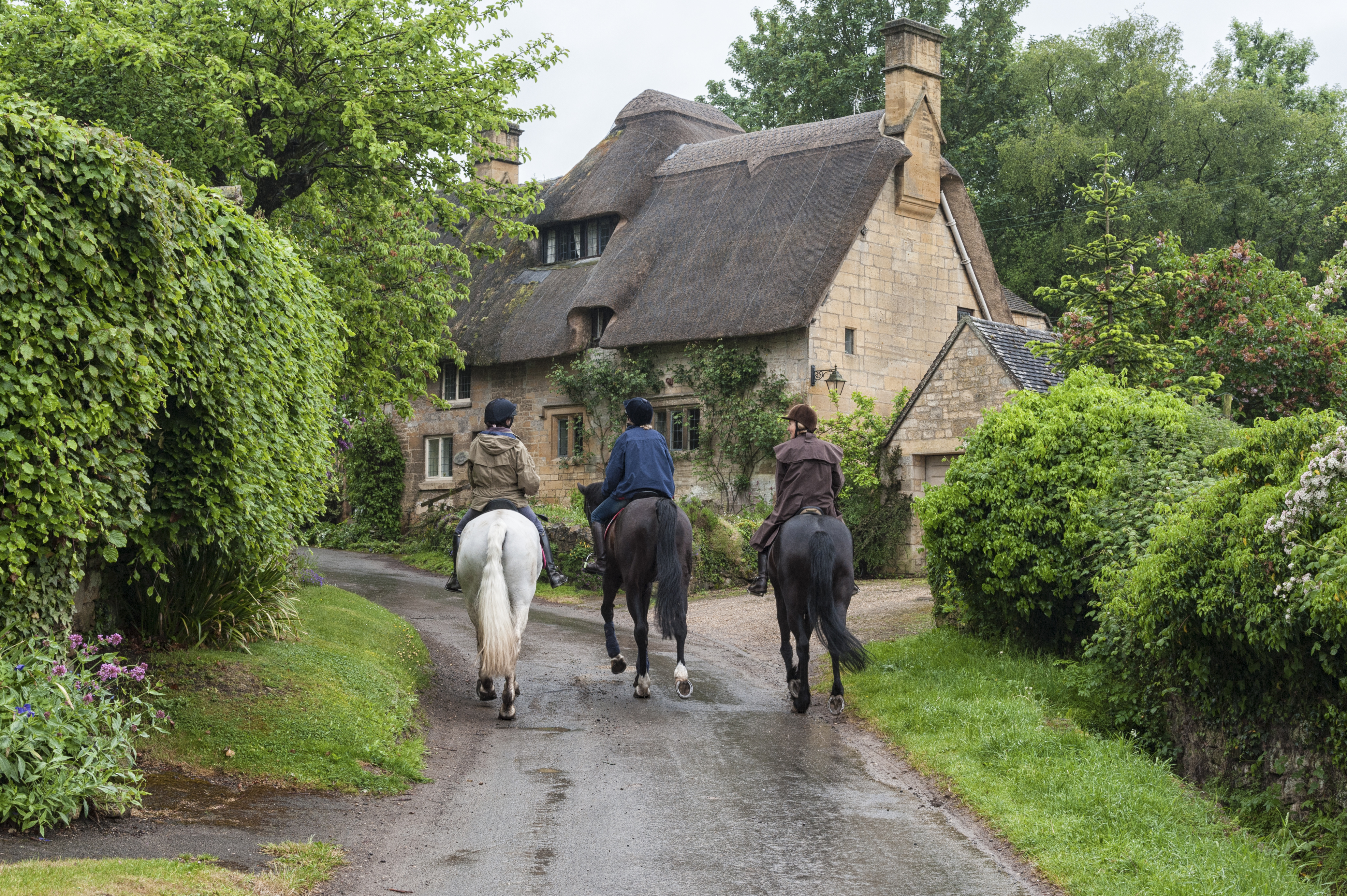 people and horses near cottages in the village of Stanton, Cotswolds district of Gloucestershire.
