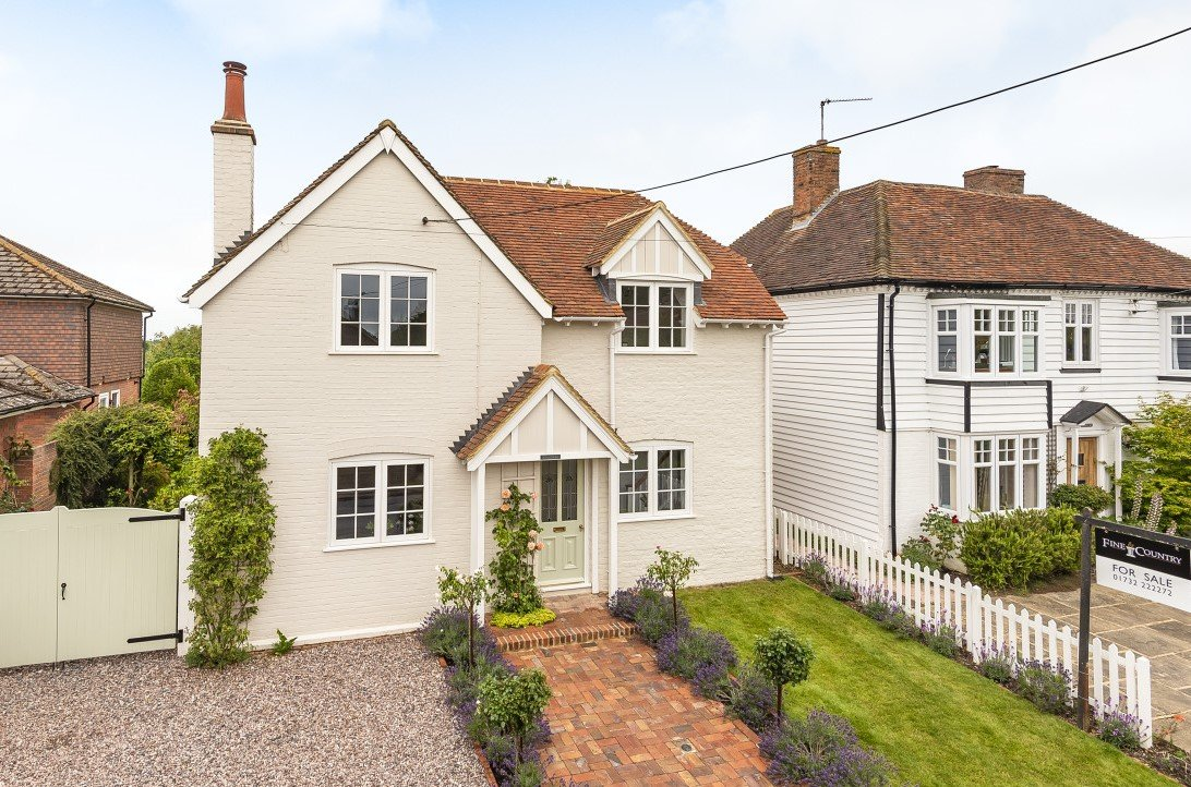 pretty converted white coach house with lavendar in spring gardens