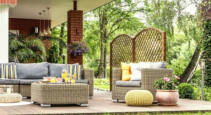 rattan_garden_furniture_with_grey_pillows_table_on_a_terrace