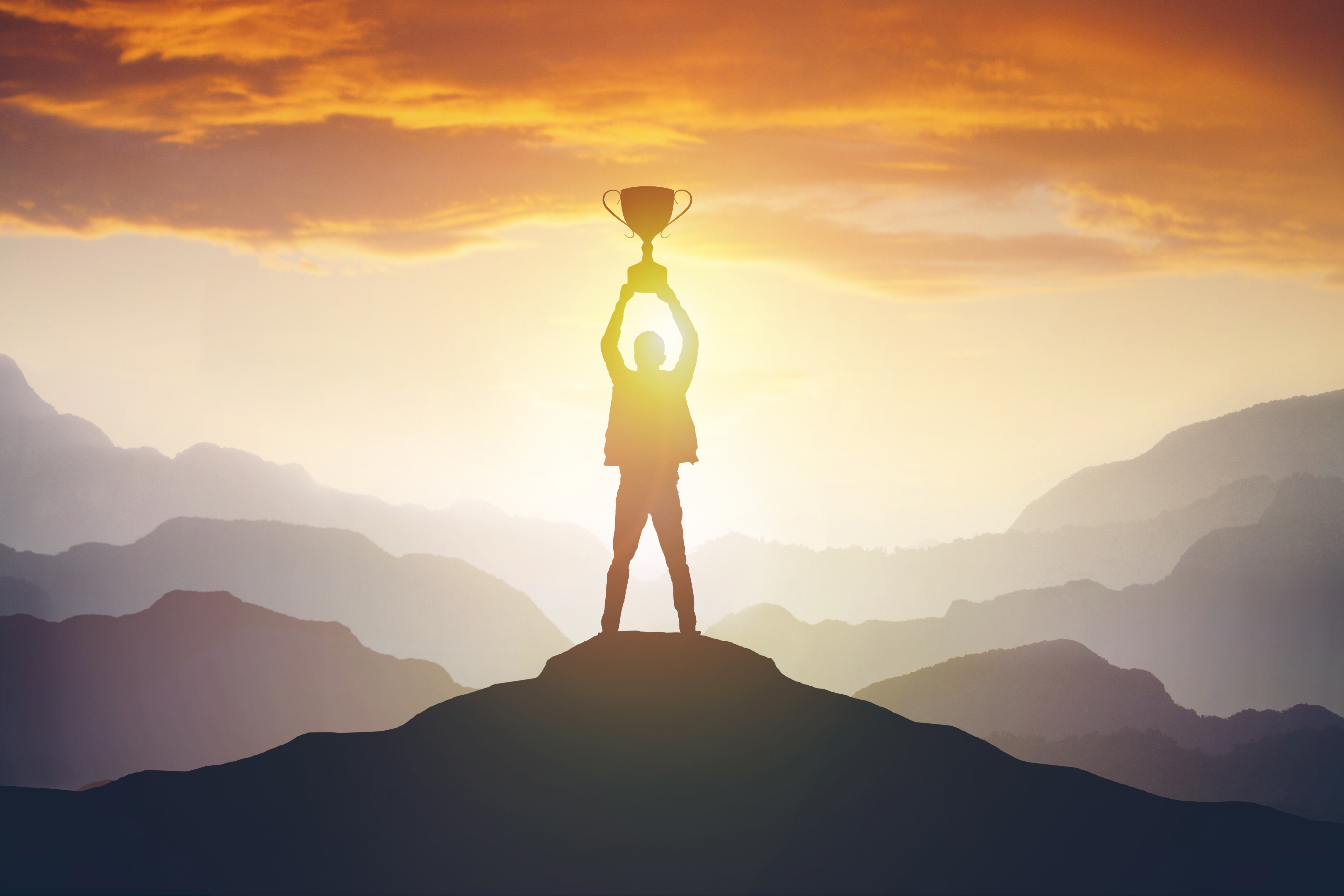 silhouette_of_a_man_holding_a_trophy_at_sunset