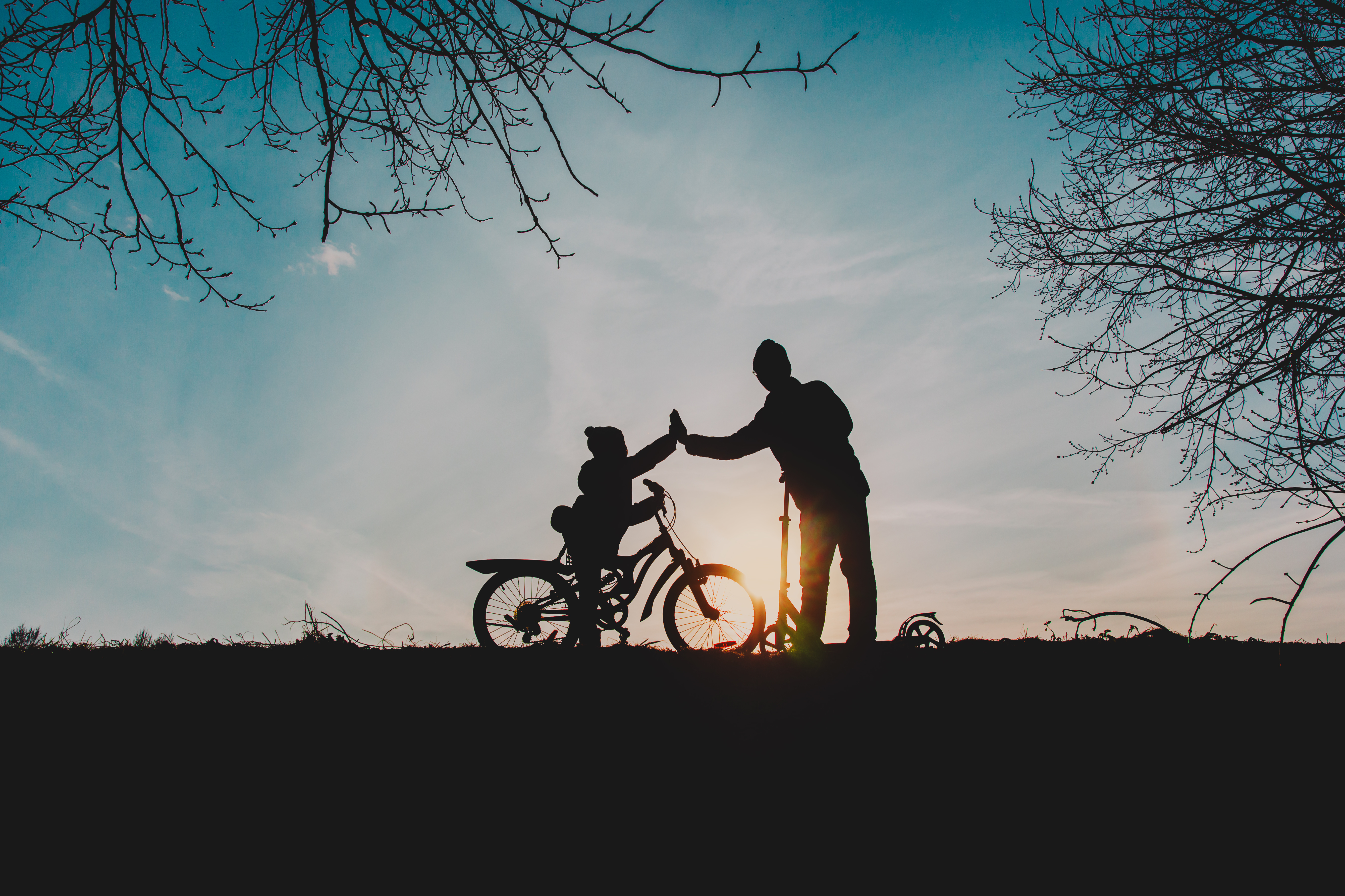 silhouette_of_happy_father_and_son_riding_bike_and_scooter_at_sunset