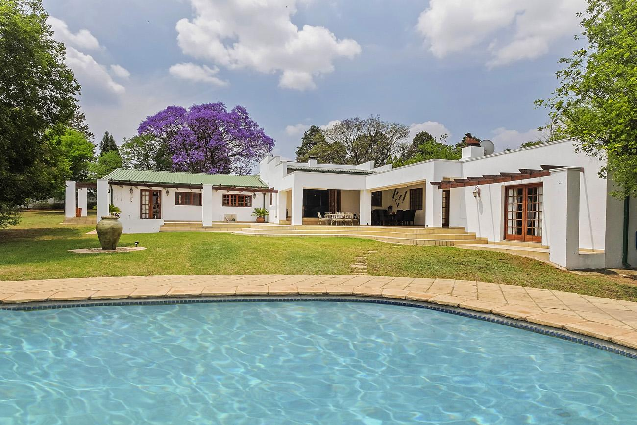 single story white villa in South Africa with purple tree and swimming pool