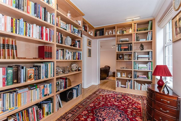 small home library with bookshelves ornaments and persian rug