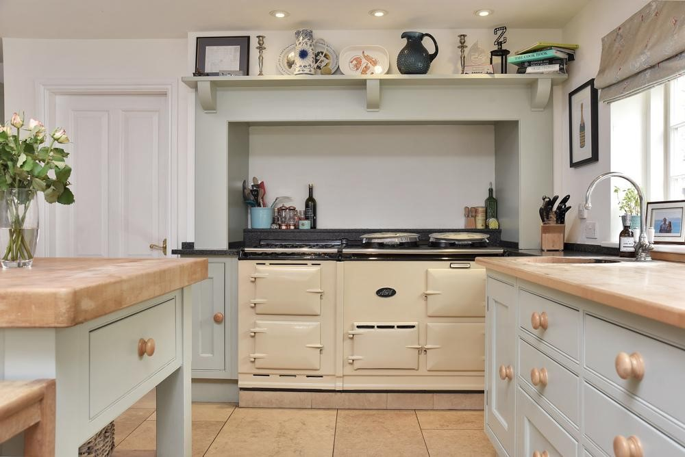 traditional large four door cream aga in english shaker kitchen putty paint wooden cabinets