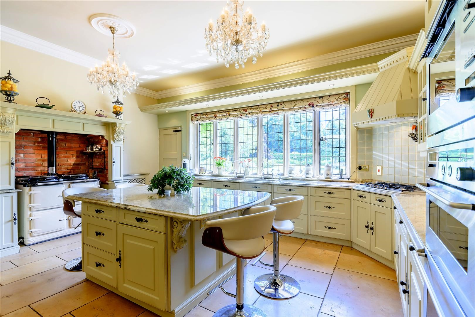 traditional luxury English country manor home kitchen with chandeliers