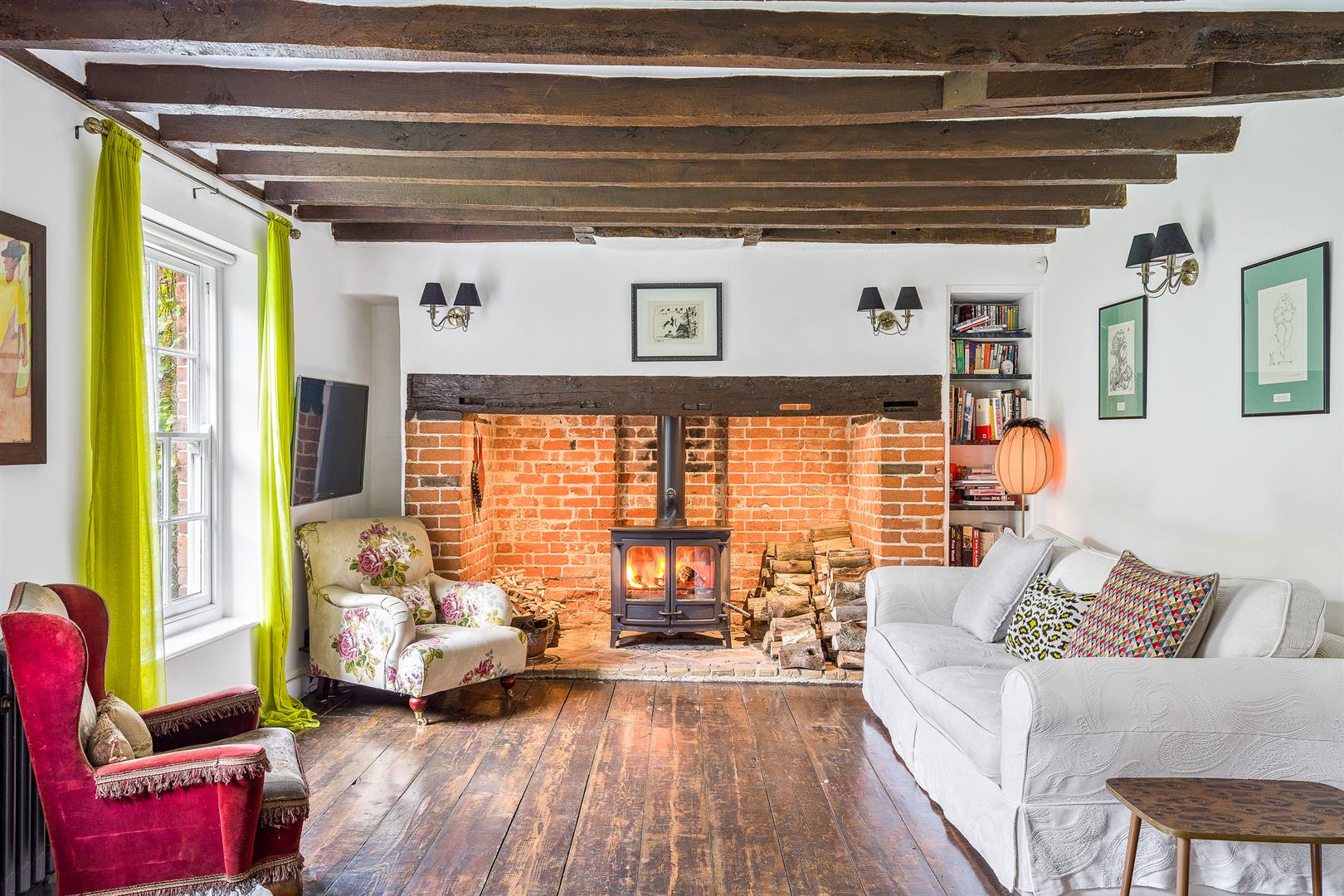 Traditional open Inglenook fireplace with wood burning stove in cottage