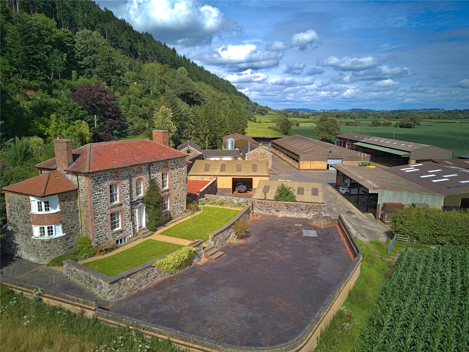Welsh stone built farmhouse in rural countryside with woodland