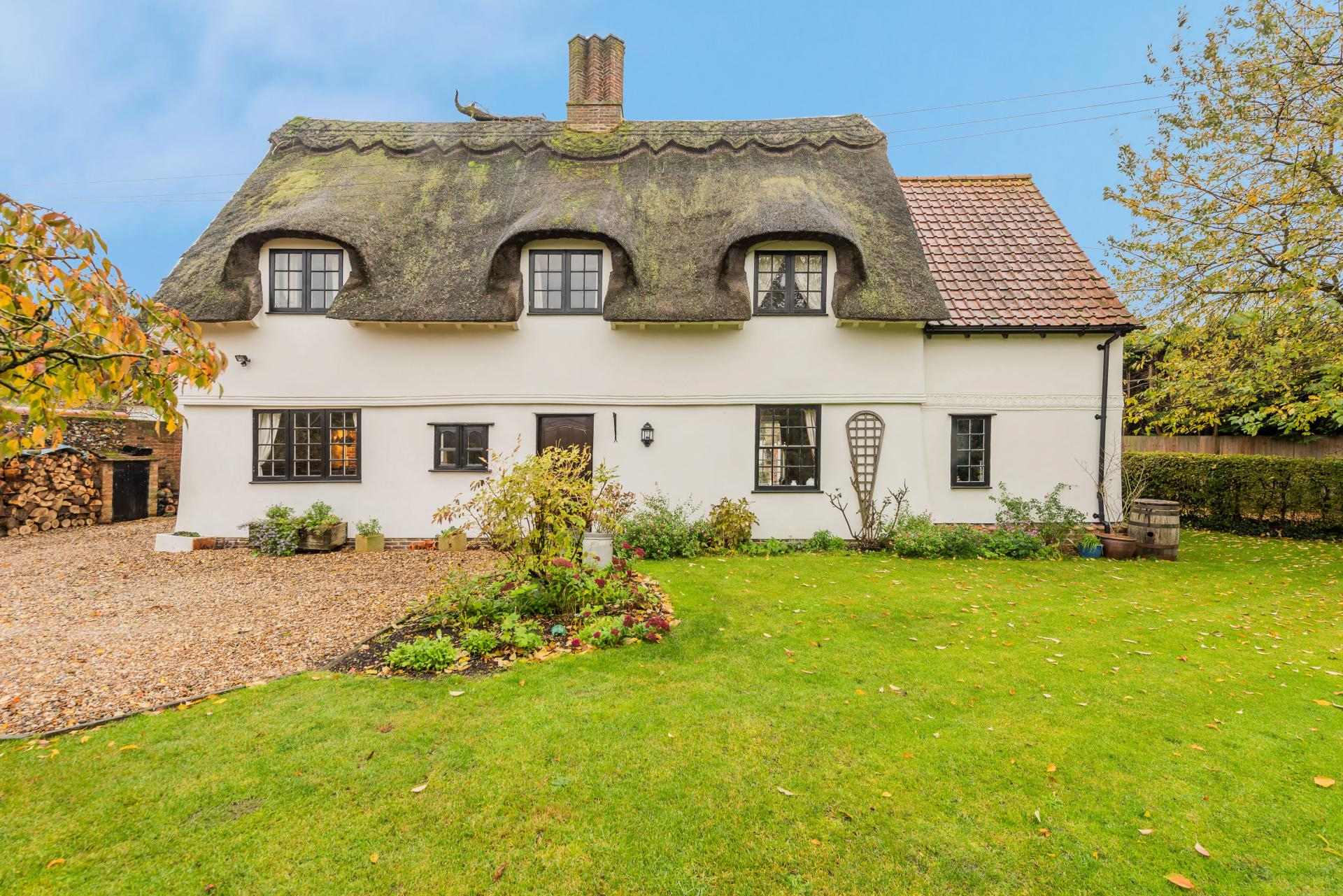 white chocolate box countryside cottage with black thatched roof and English country garden