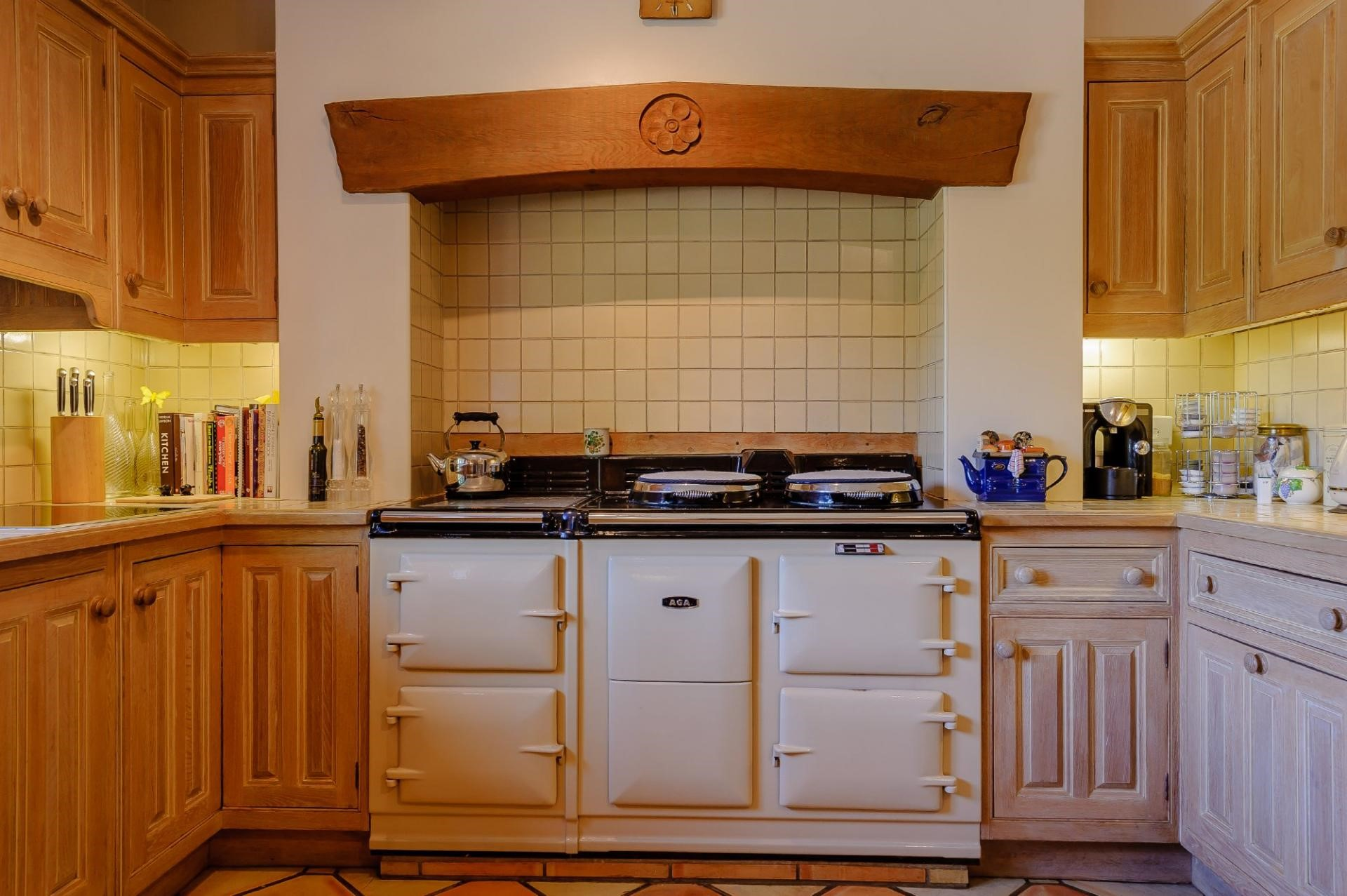 white cream AGA in Inglenook fireplace in traditional unpainted shaker kitchen