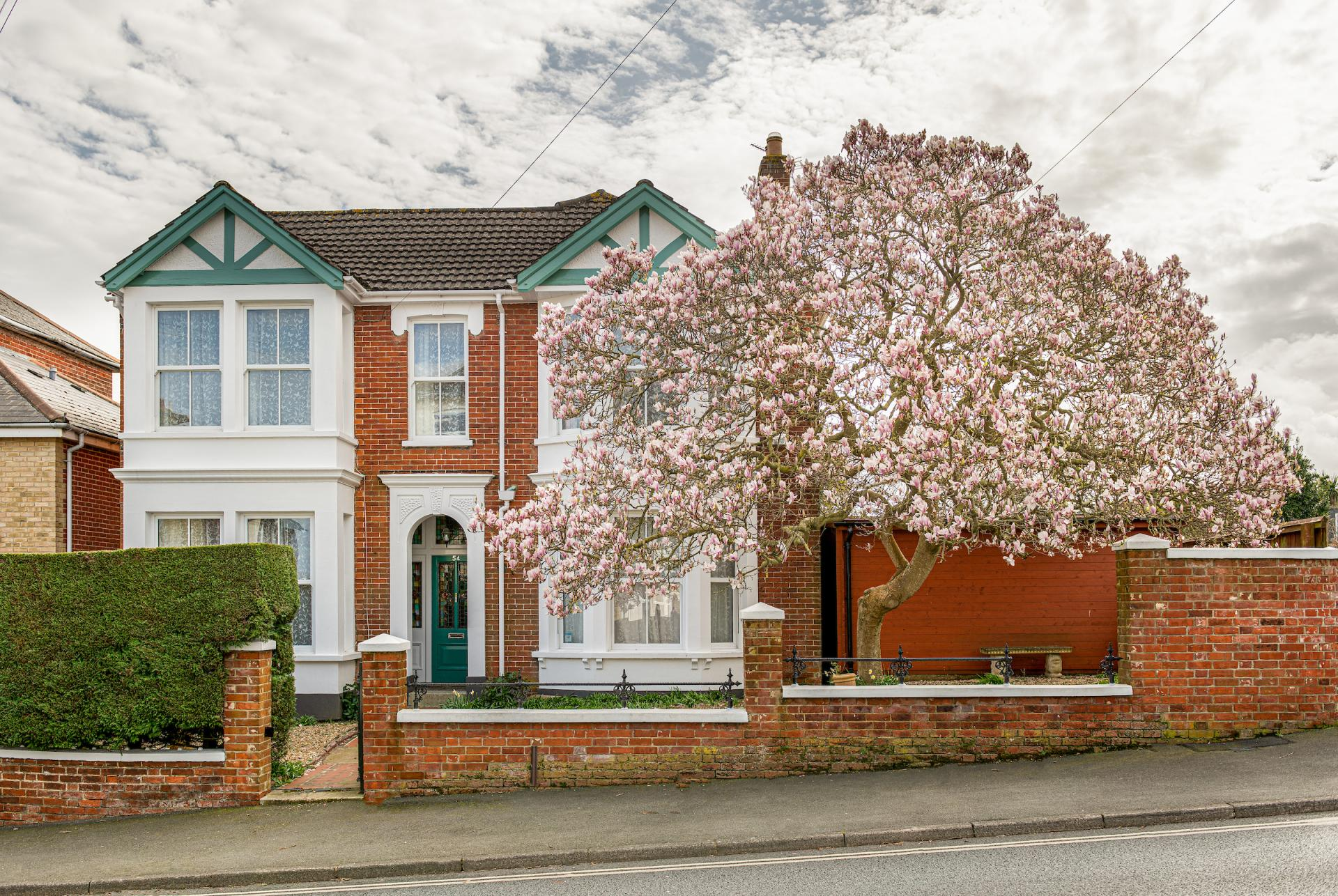 beautiful brick Victorian semi detached terrace house with pink blossom tree