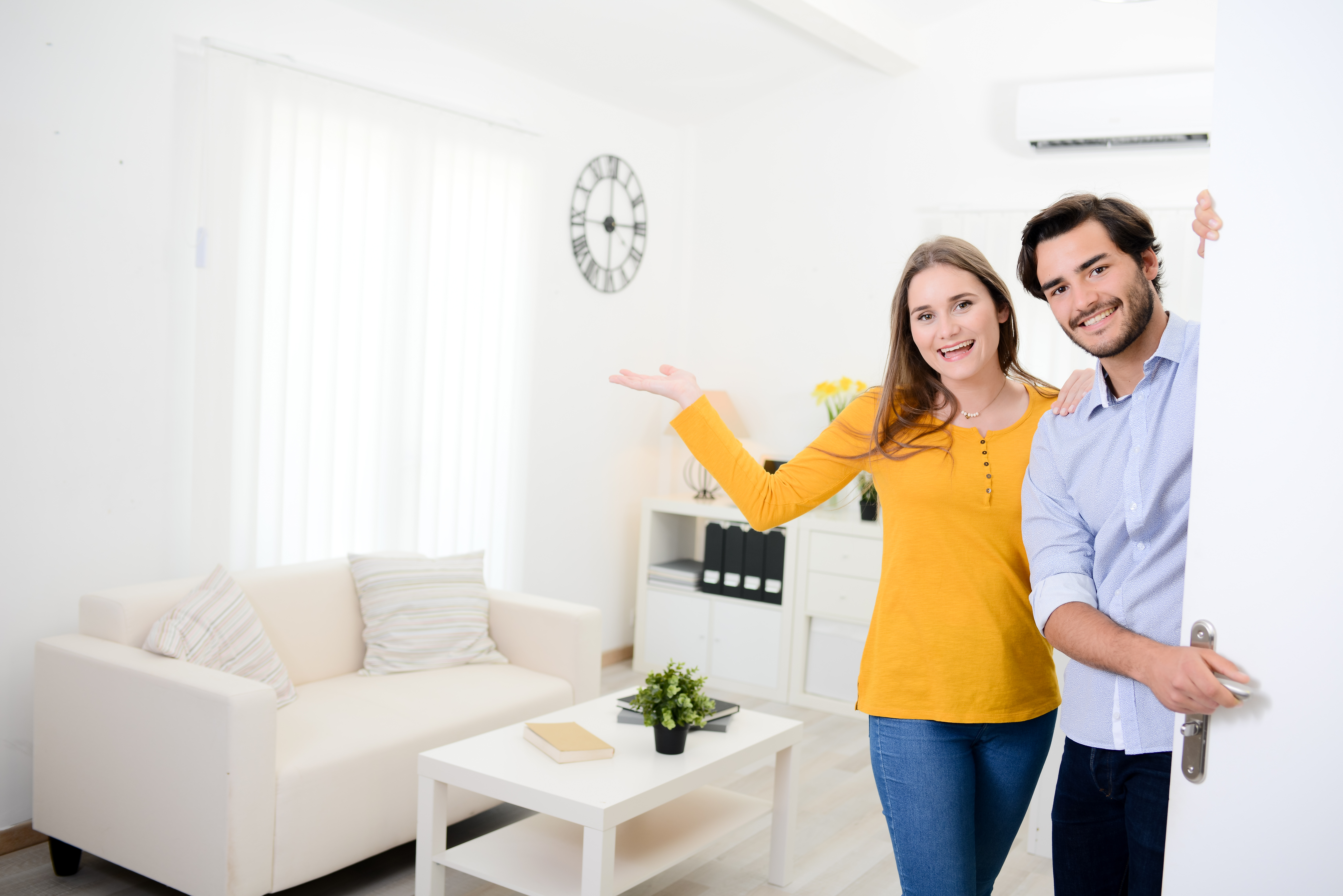 cheerful young couple man and woman welcome  at open front door new home apartment