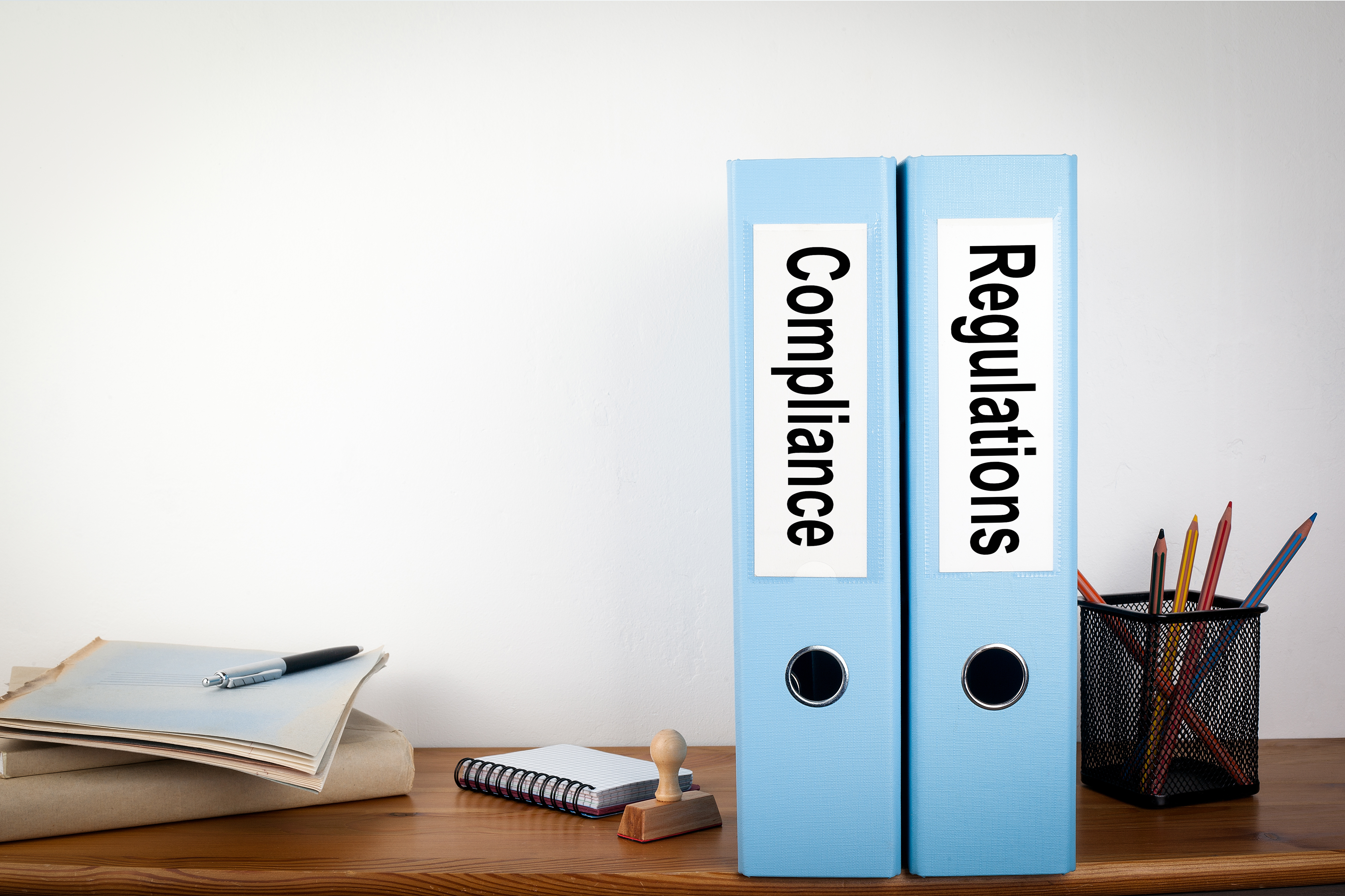 Compliance and Regulations binders in the office. Stationery on a wooden shelf