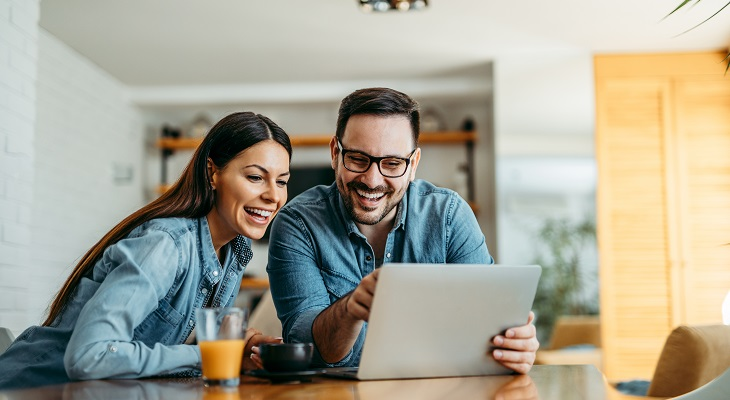 couple_looking_at_laptop_computer_together_at_home_front_view_portrait