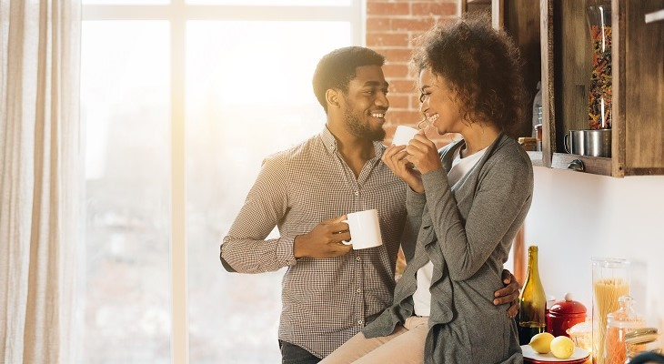 cute_young_couple_drinking_coffee_in_kitchen