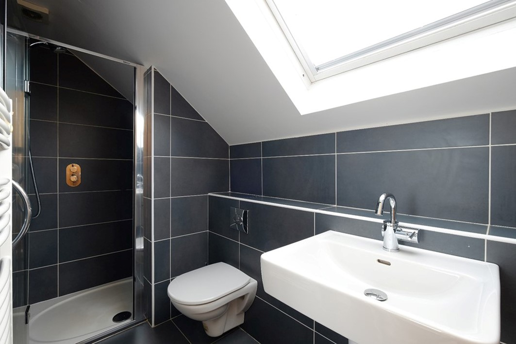 dark grey tile stylish simple loft bathroom with skylight