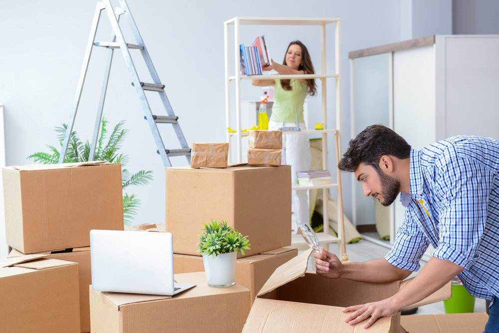 couple unpacking boxes in new house