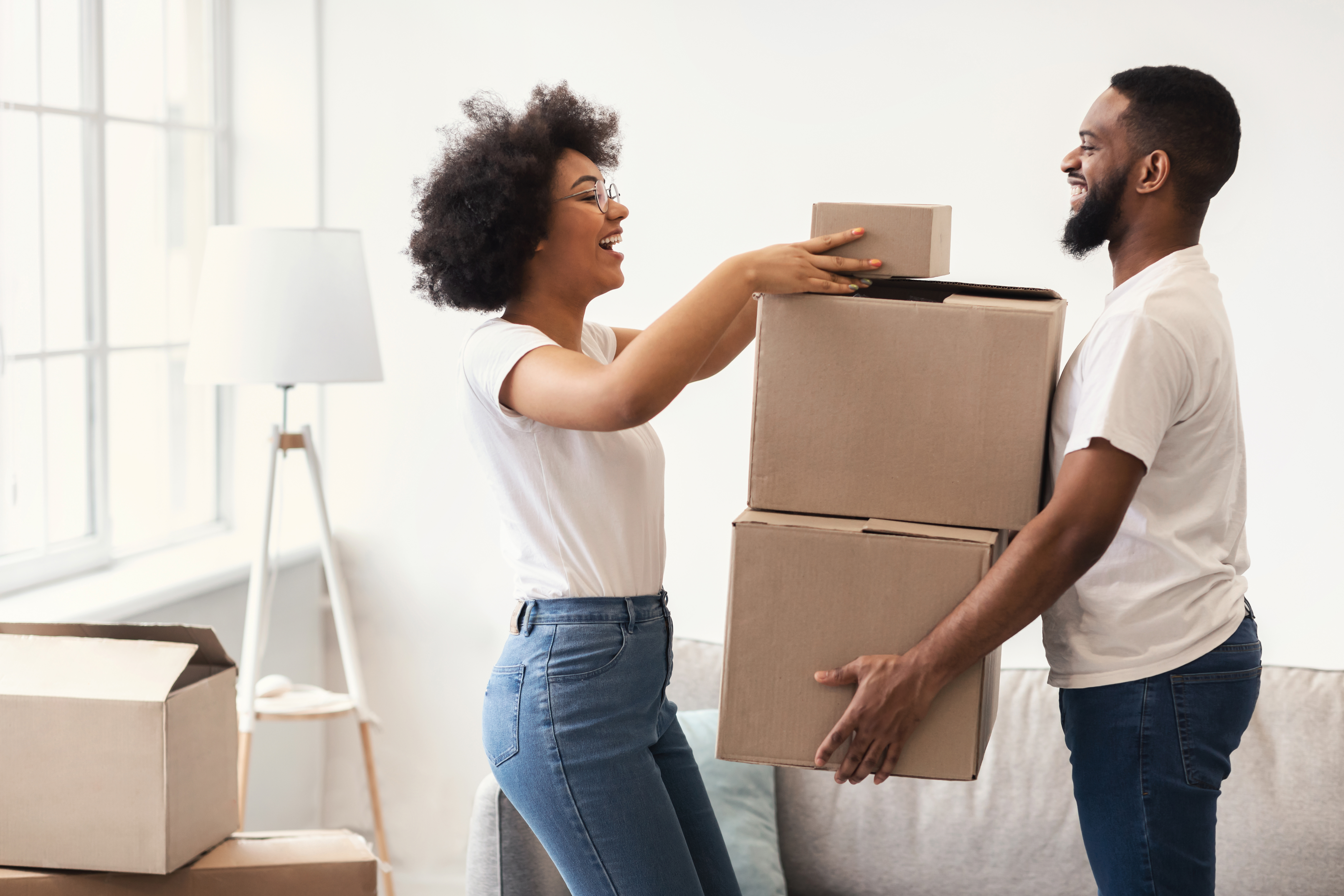 Happy Couple Packing Moving Boxes Together Standing Indoors