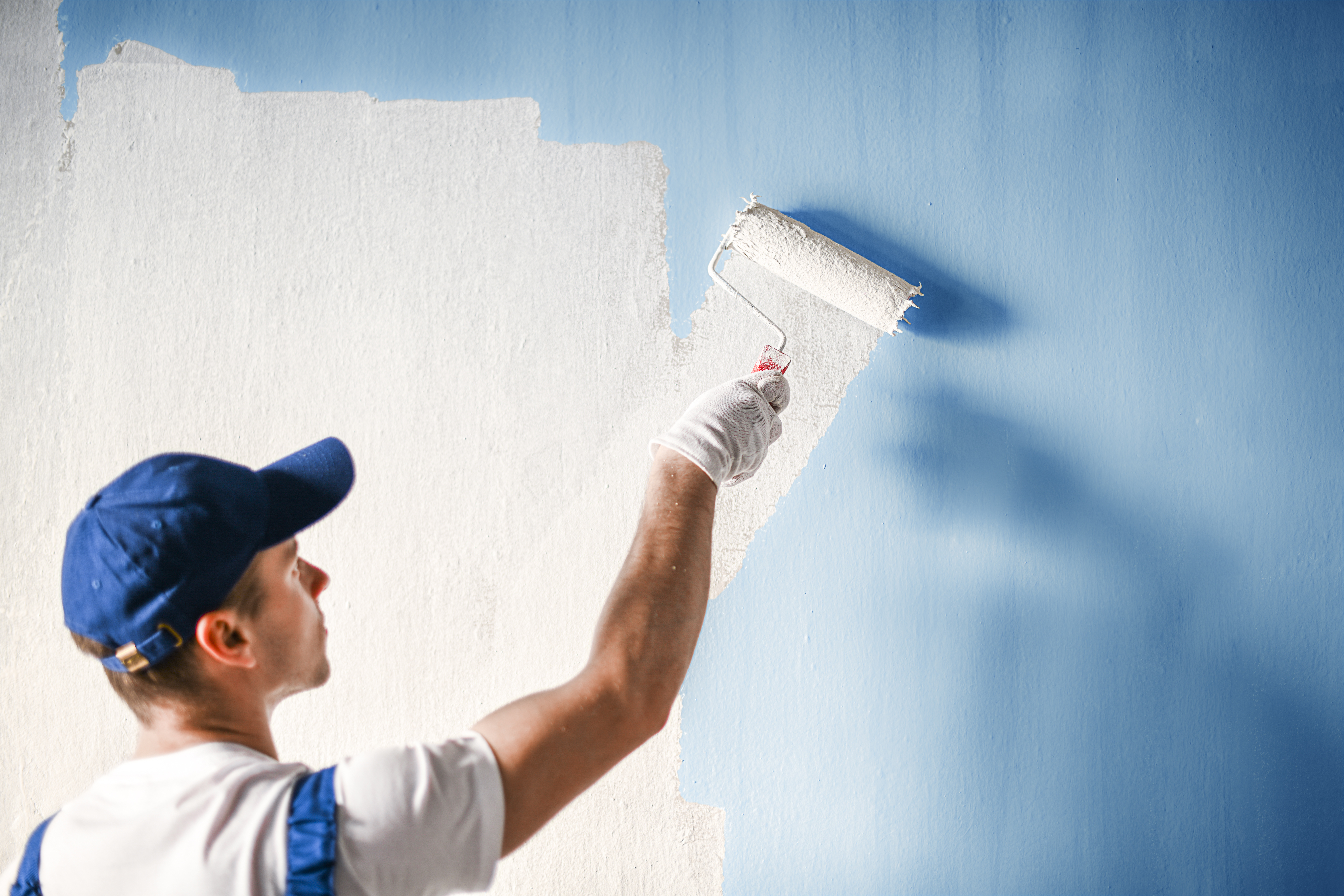 man DIY painting blue walls white