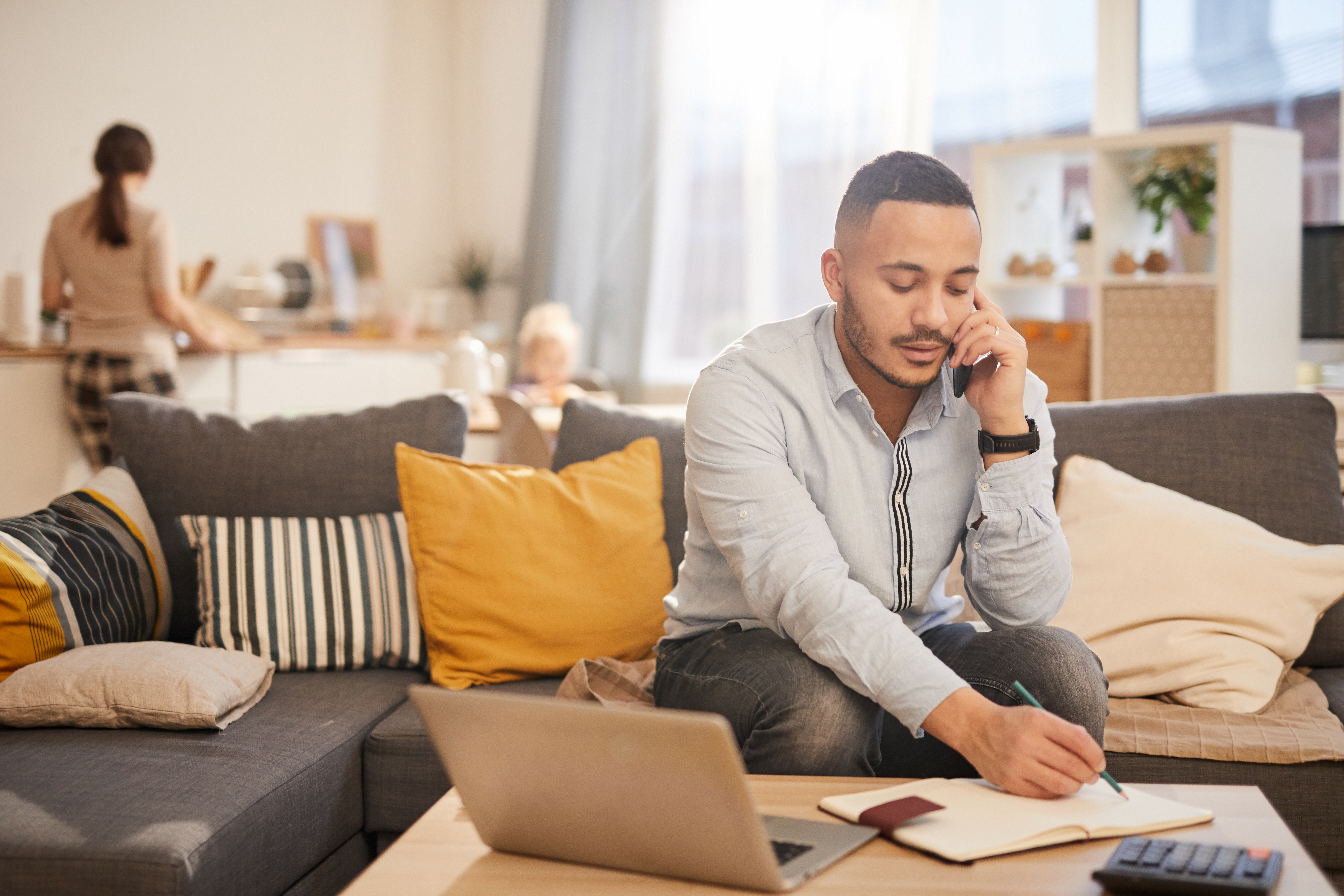 man speaking by phone while working from home in cozy interior, copy space
