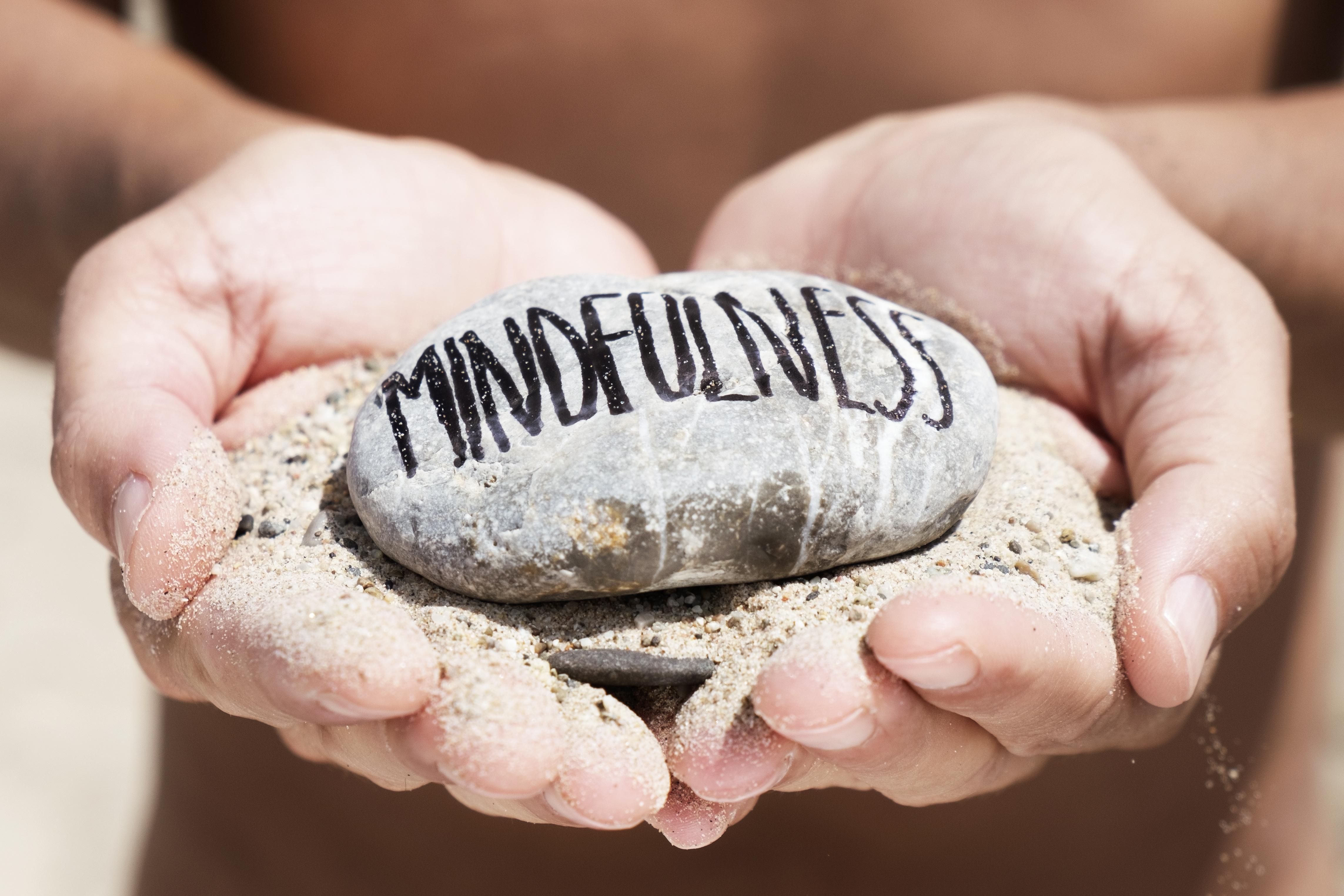mindfulness sand holding pebble