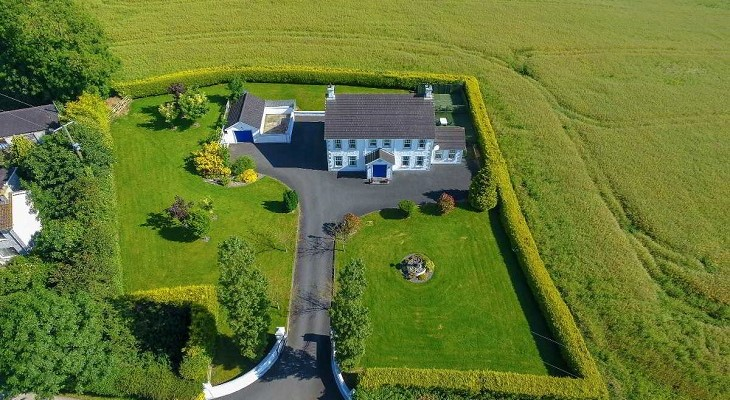 northern_ireland_country_farmhouse_in_lush_green_countryside_aerial