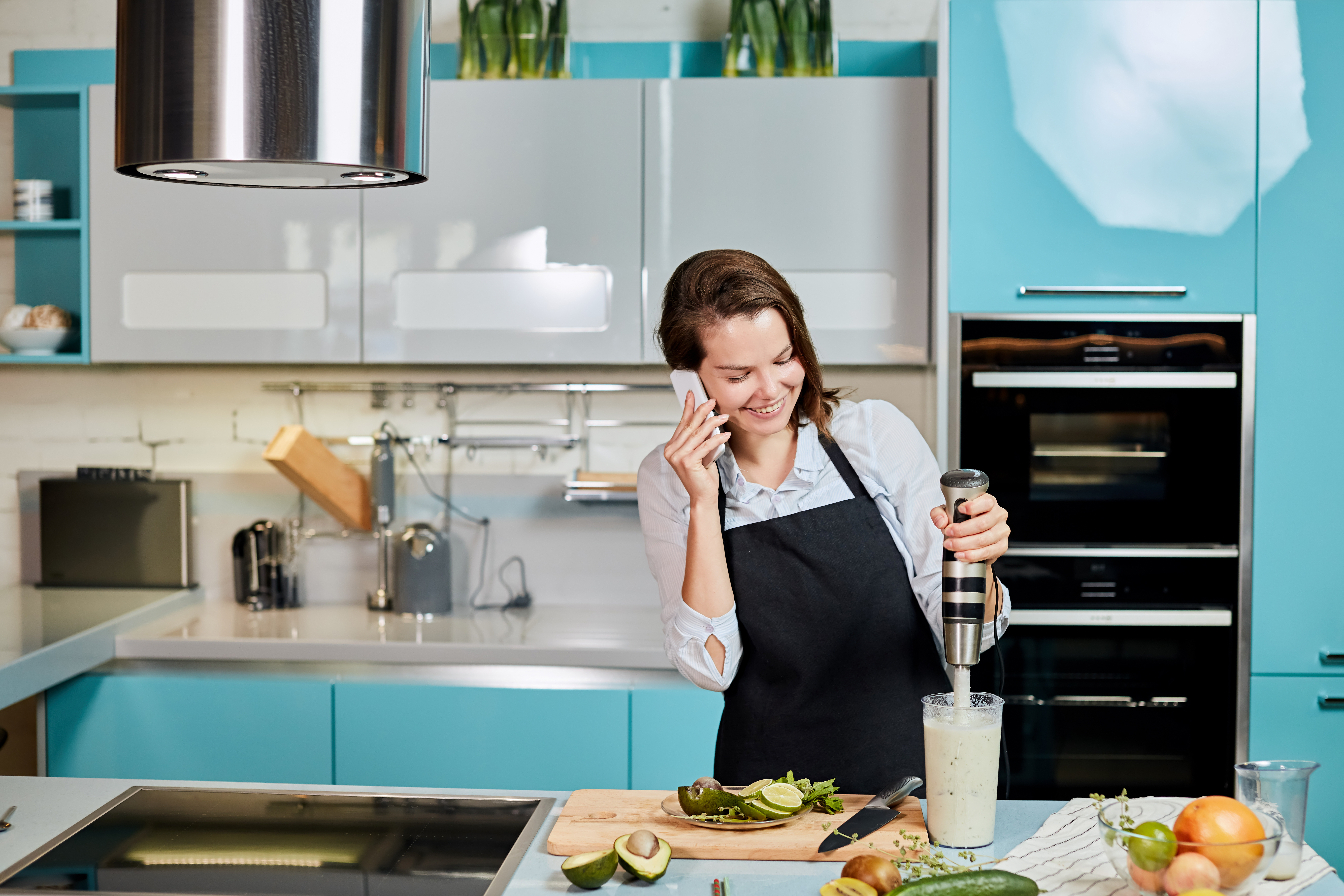 happy woman on the phone making lunch or dinner in a modern blue kitchen