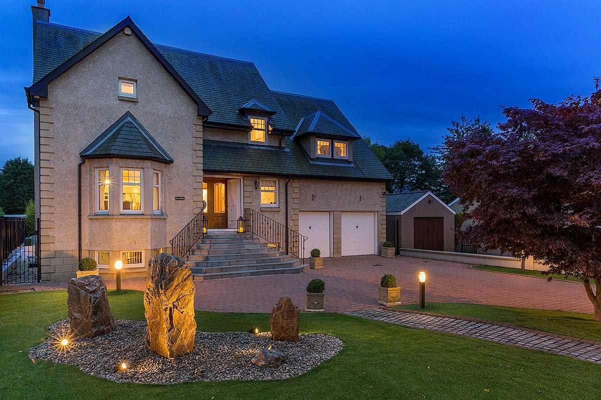 unique pebble large family home with landscaped front garden night with lights