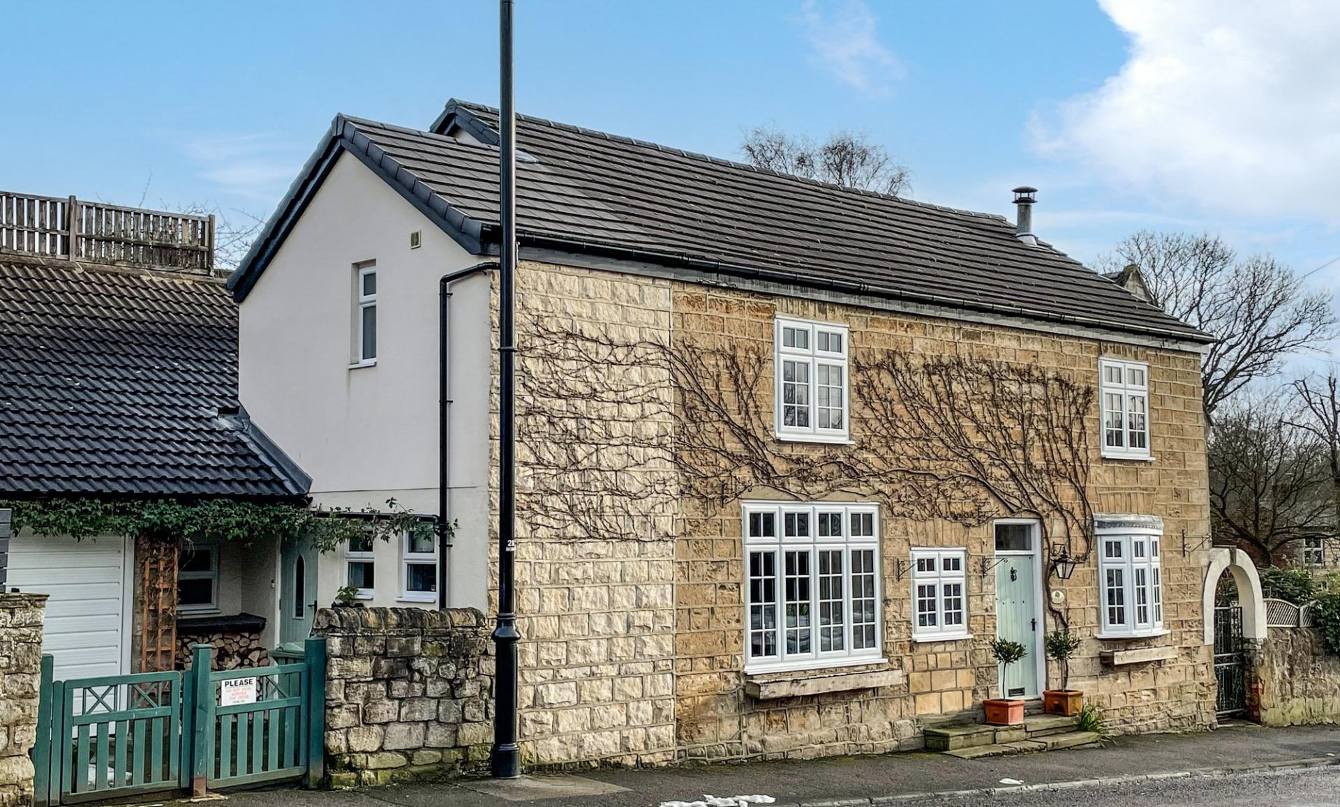 West Yorkshire stone built charming village cottage with blue door.