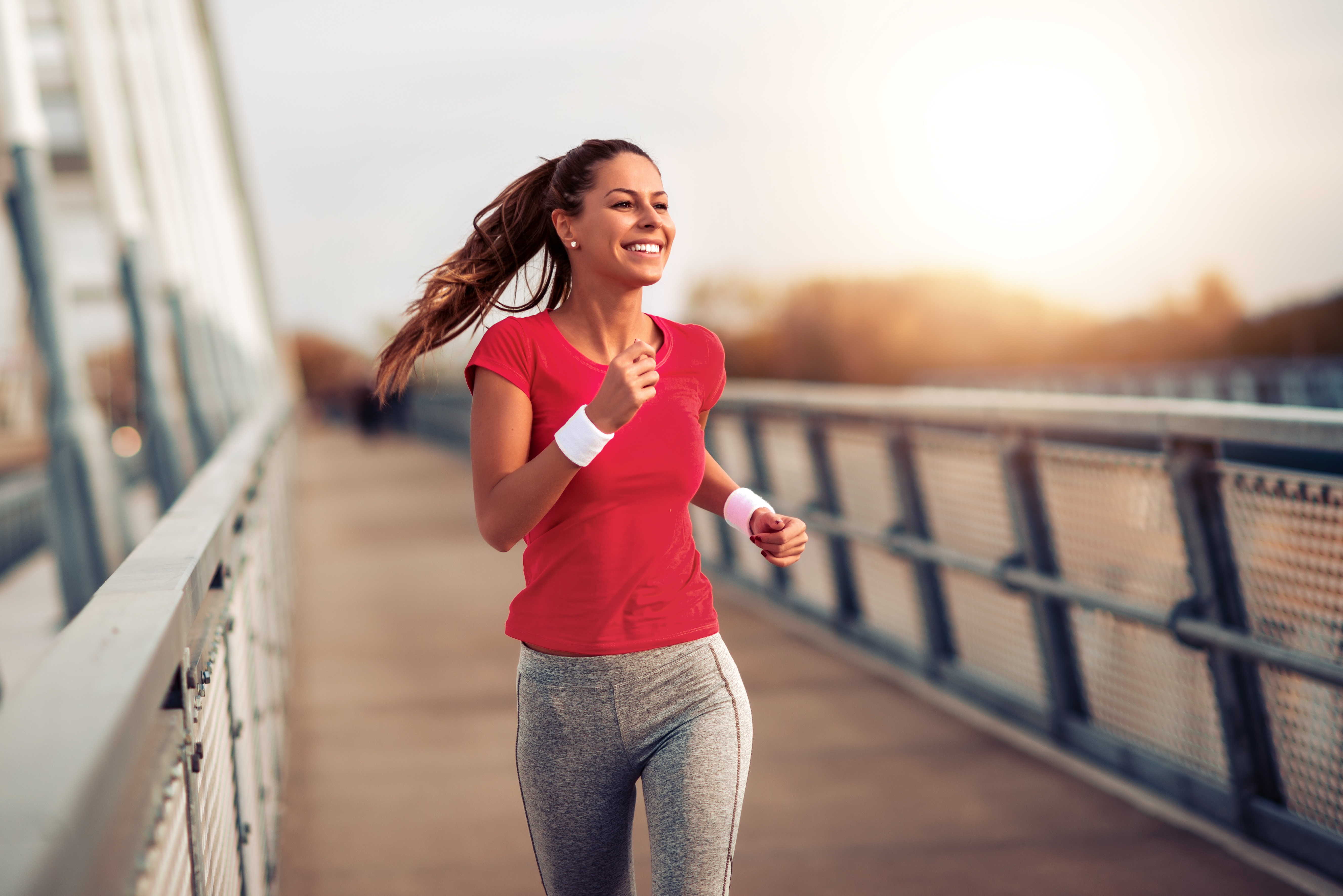 happy woman running excercising on her commute on a bridge by the water