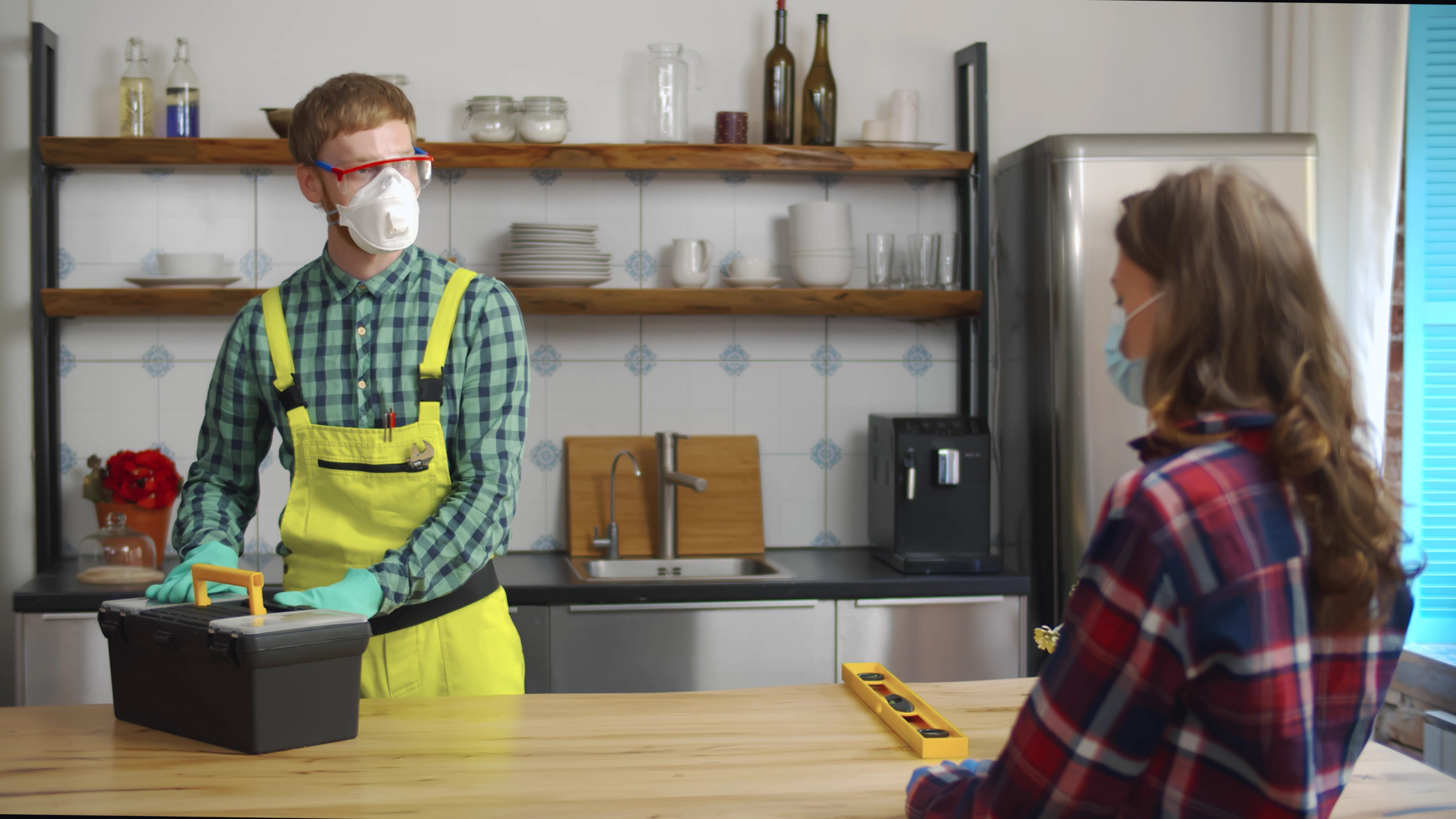 Woman welcome repairman at home wearing protective masks