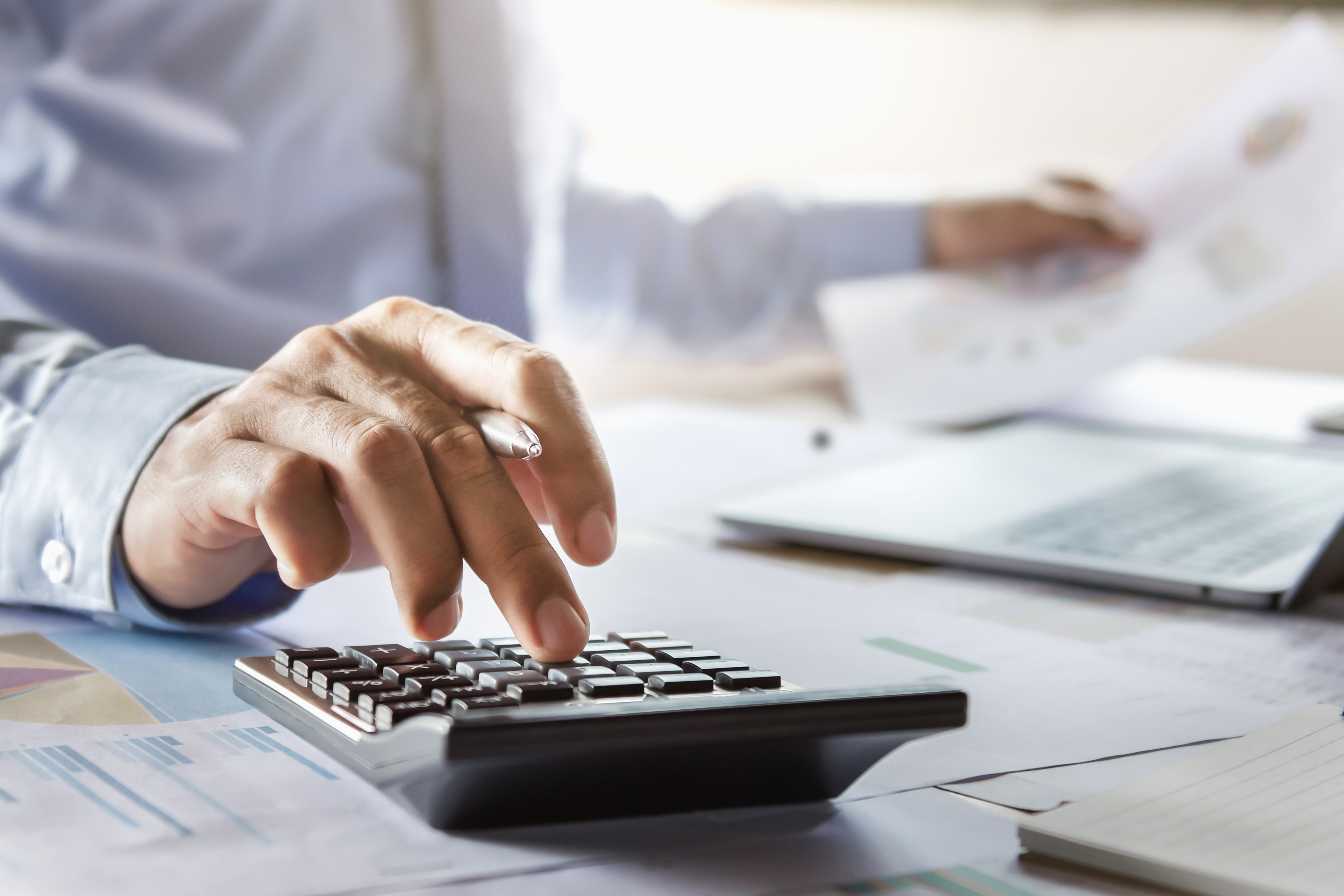 business man adding fees on calculator with documents