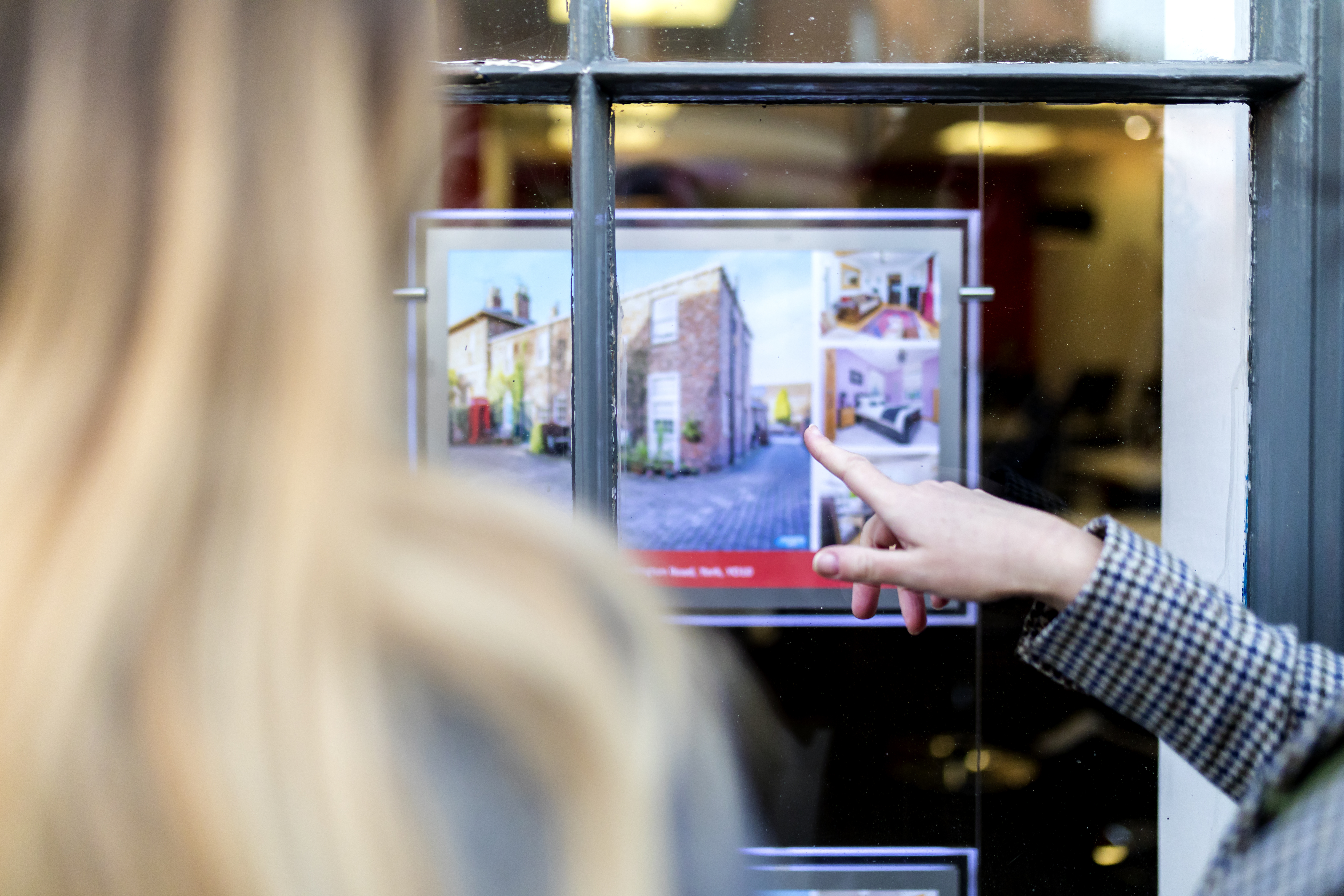 Couple looking at a property advert in the window of an estate agents or real estate shop window in England