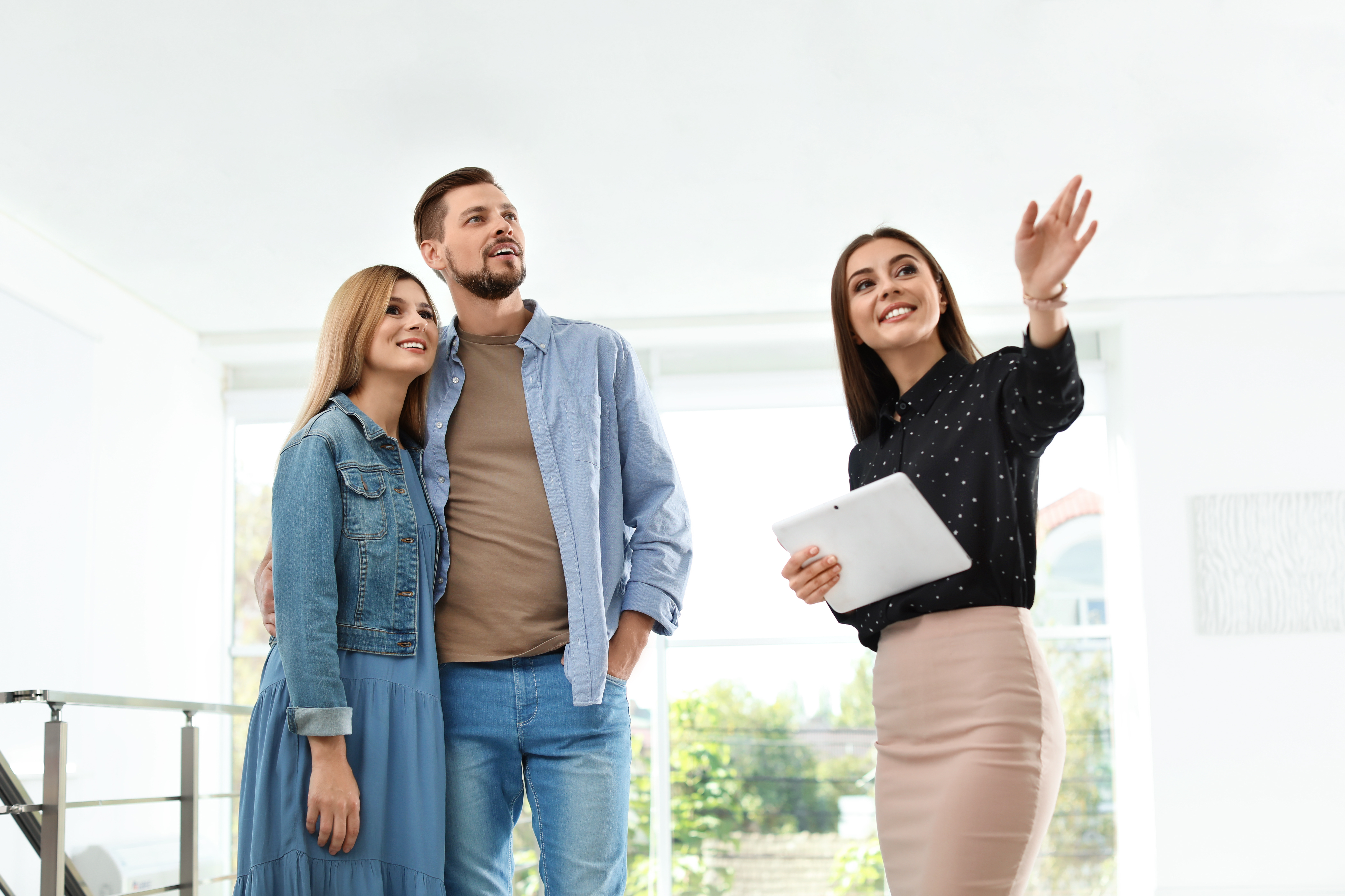 Female real estate agent showing new house to couple