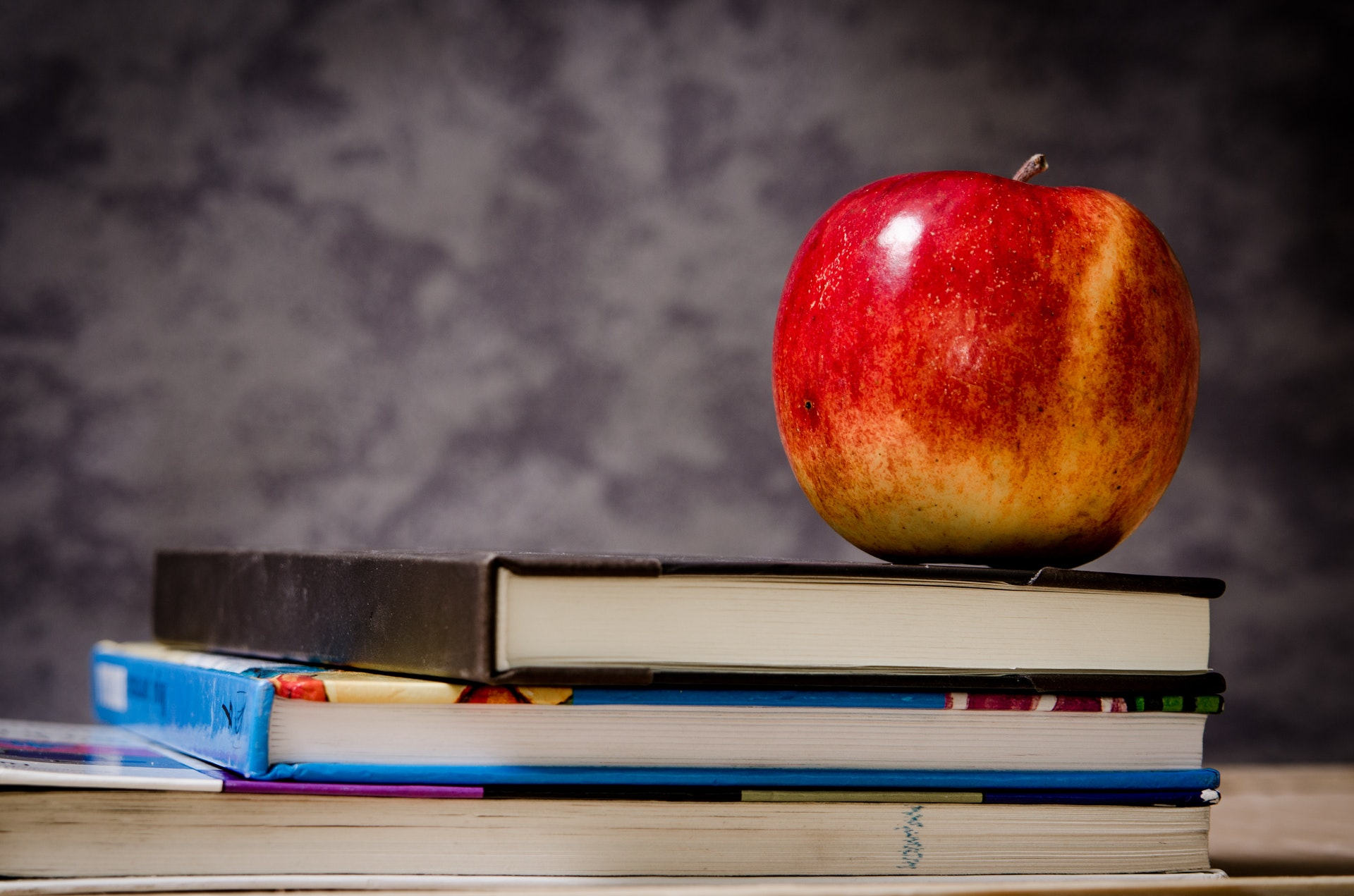 close-up-of-apple-on-top-of-books-256520_hd